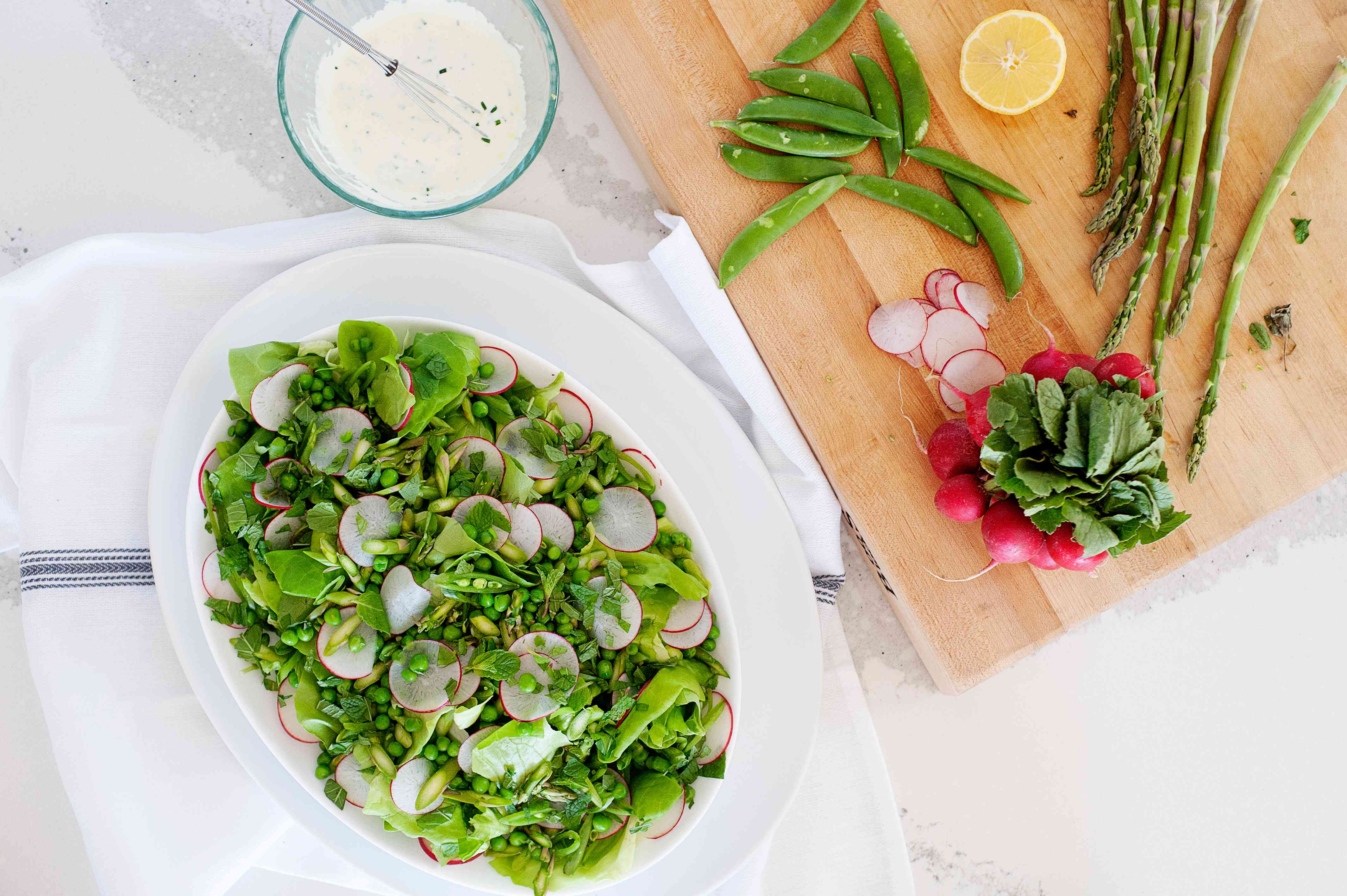 Greenest Spring Green Salad set next to a cutting board.