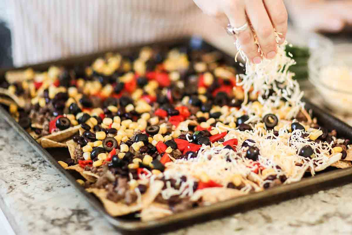 Sheet Pan Nachos with Ground Beef add the corn, black beans, olives and cheese