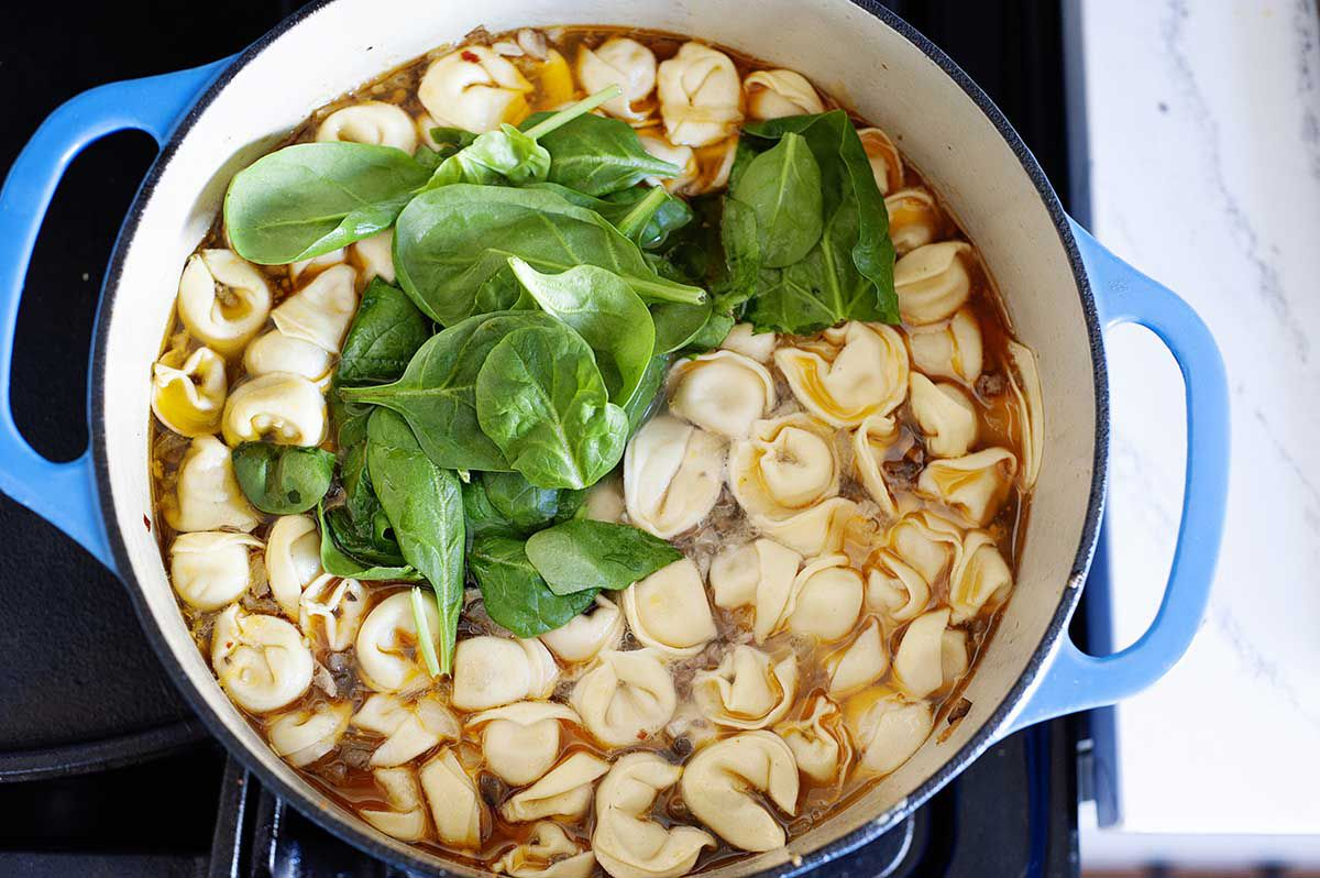 Dutch oven with the best tortellini soup simmering on the stove. Spinach is on top of the tortellini before being mixed into the soup.
