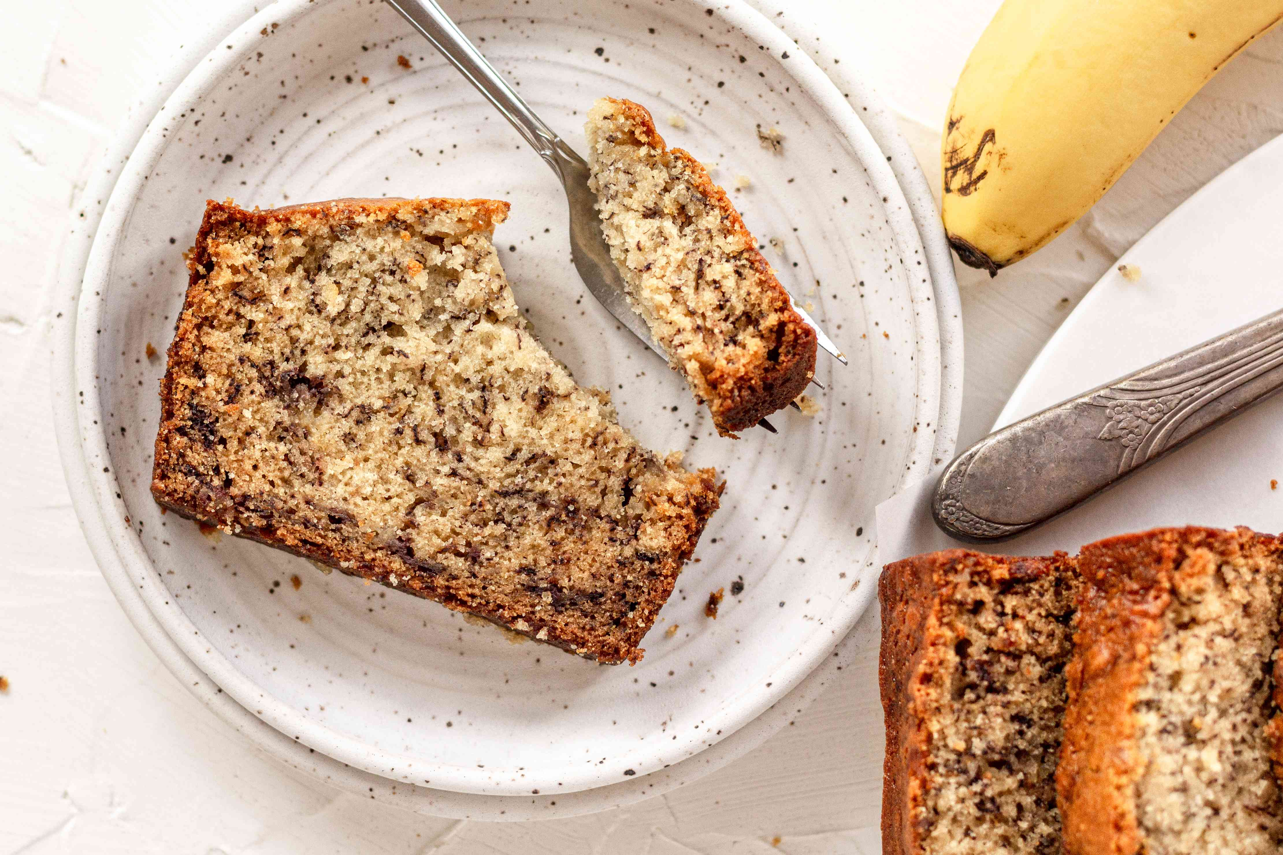 Overhead view of a slice of banana bread on a plate.