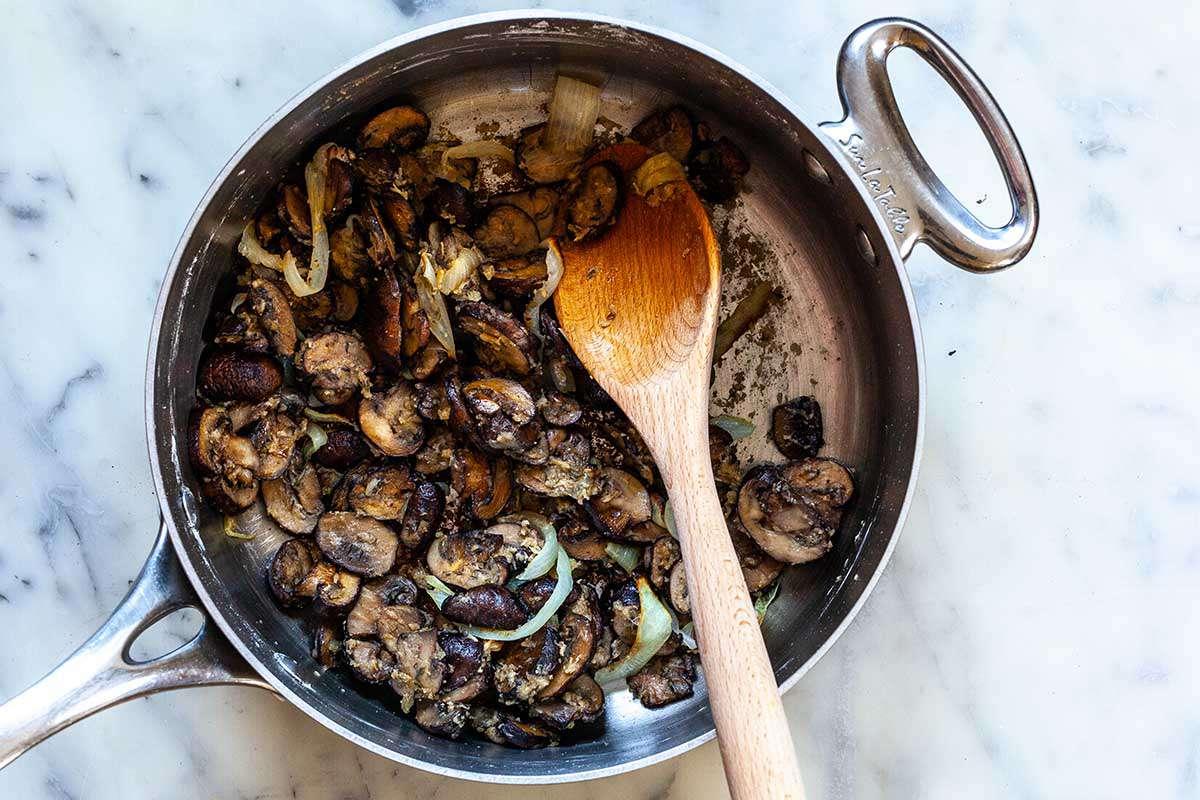 Mushrooms being sauteed in a silver skillet to make homemade vegan mushroom gravy