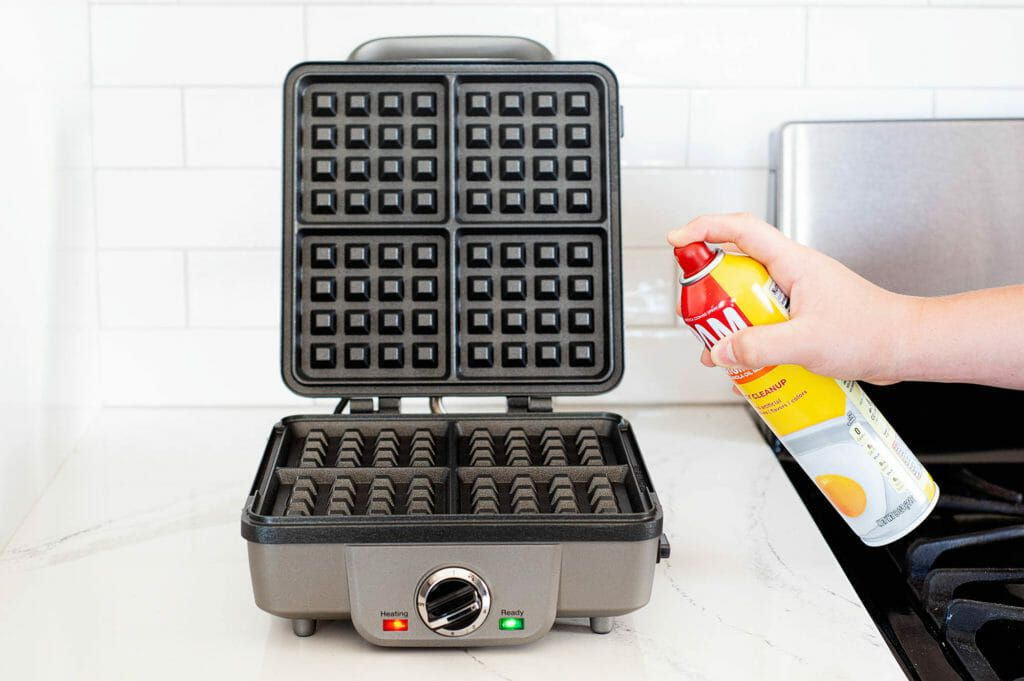 Cooking spray is being sprayed on an open waffle maker.
