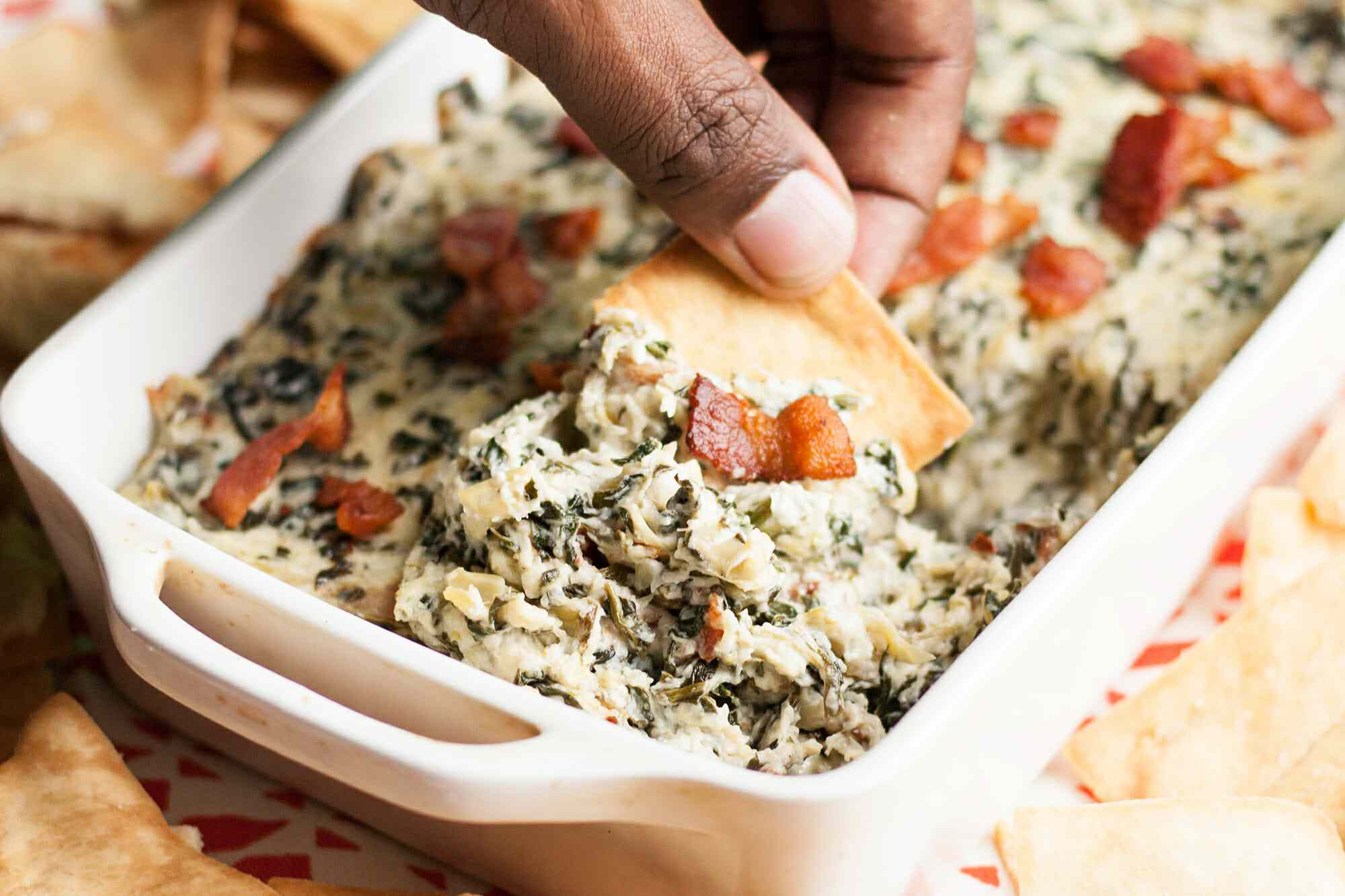 Easy Spinach Artichoke Dip with Bacon in a white casserole dish