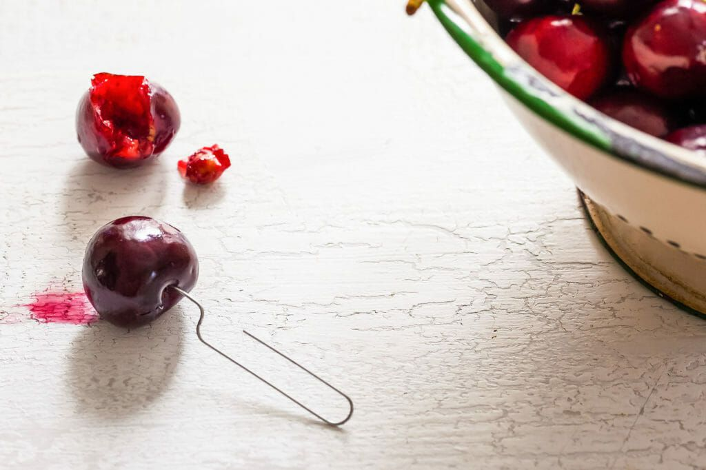 Best way to pit cherries with a straightened paper clip poked inside a cherry. A pitted cherry is behind it along with a large bowl of cherries.