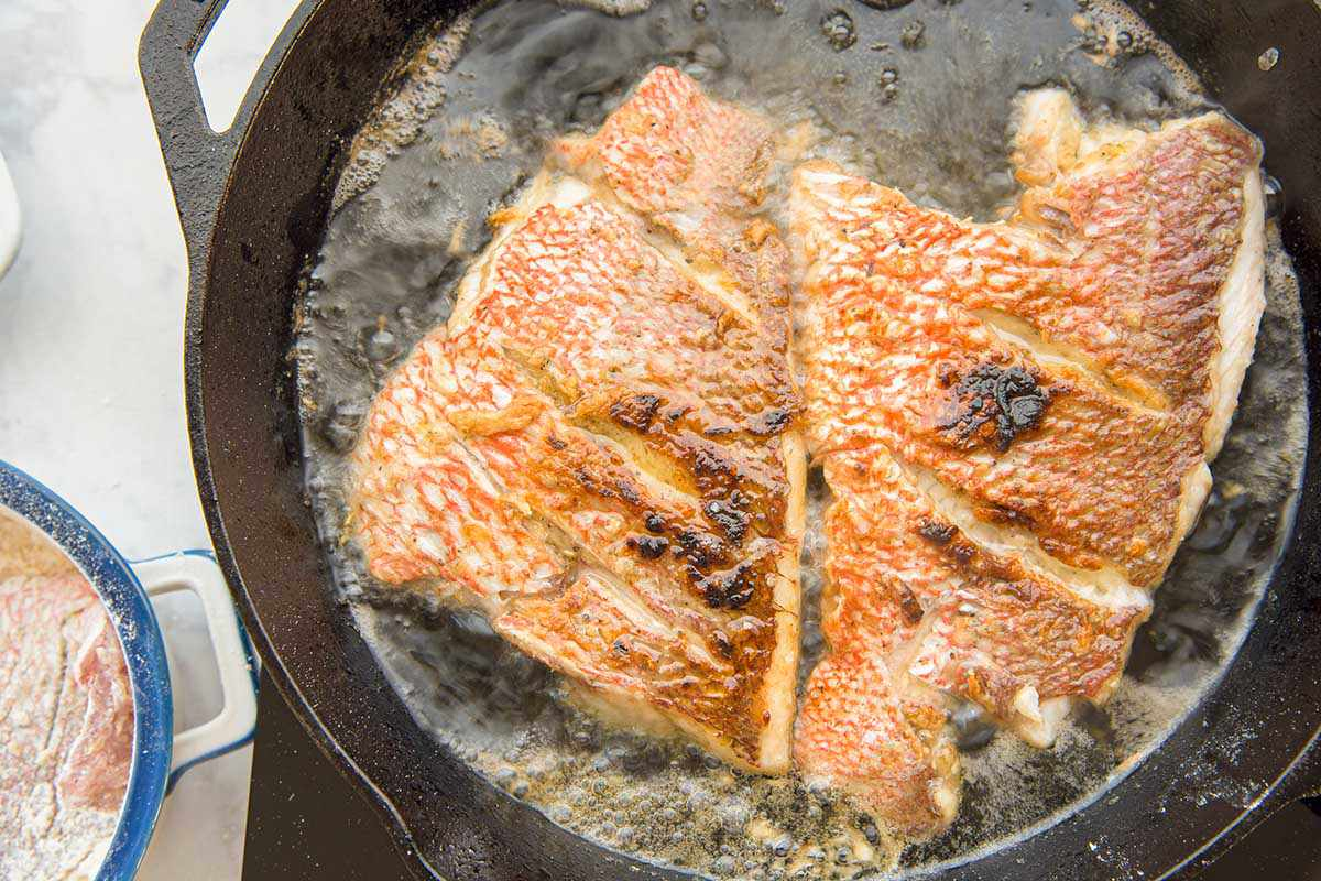 Red snapper with garlic sauce frying in a cast iron skillet. Two fillets are side by side in the pan and liquid is simmering in the pan.