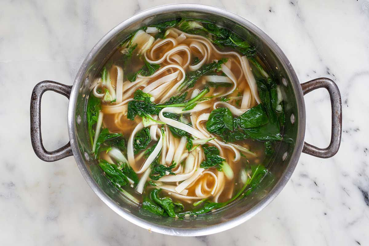 Udon noodles, spinach and fresh herbs in a soup pot.