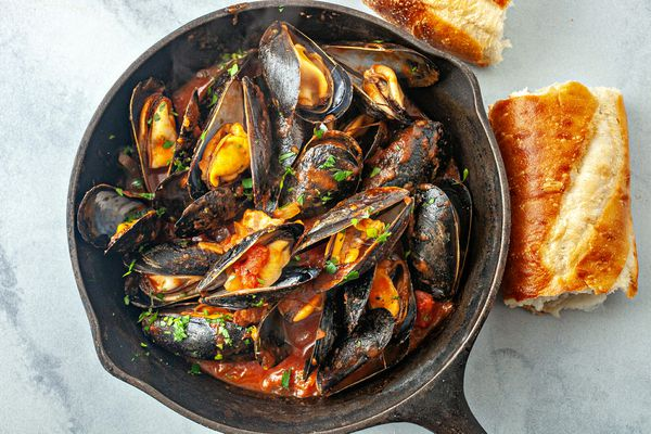 Mussels in tomato sauce recipe - overhead photo of mussels in cast iron pan with bread