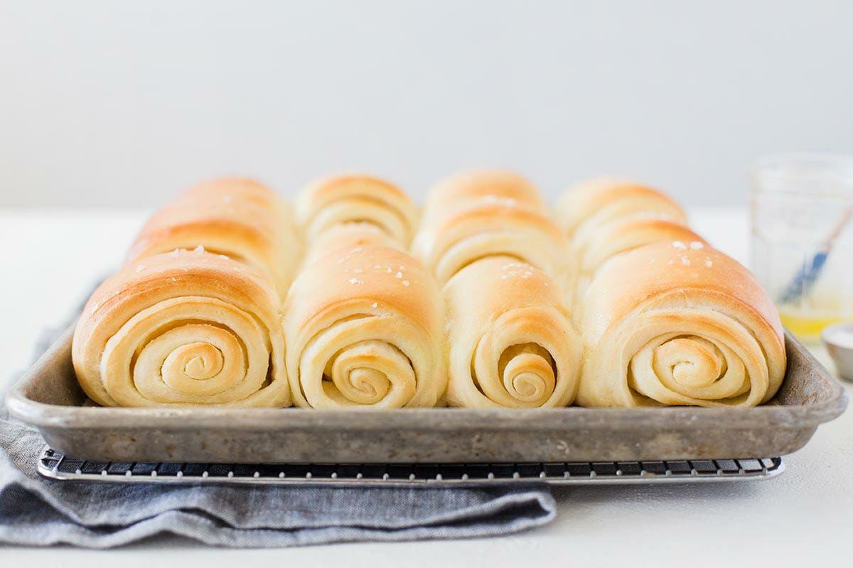 Utah's Famouse Lion House Rolls on a baking sheet set on a cooling rack.