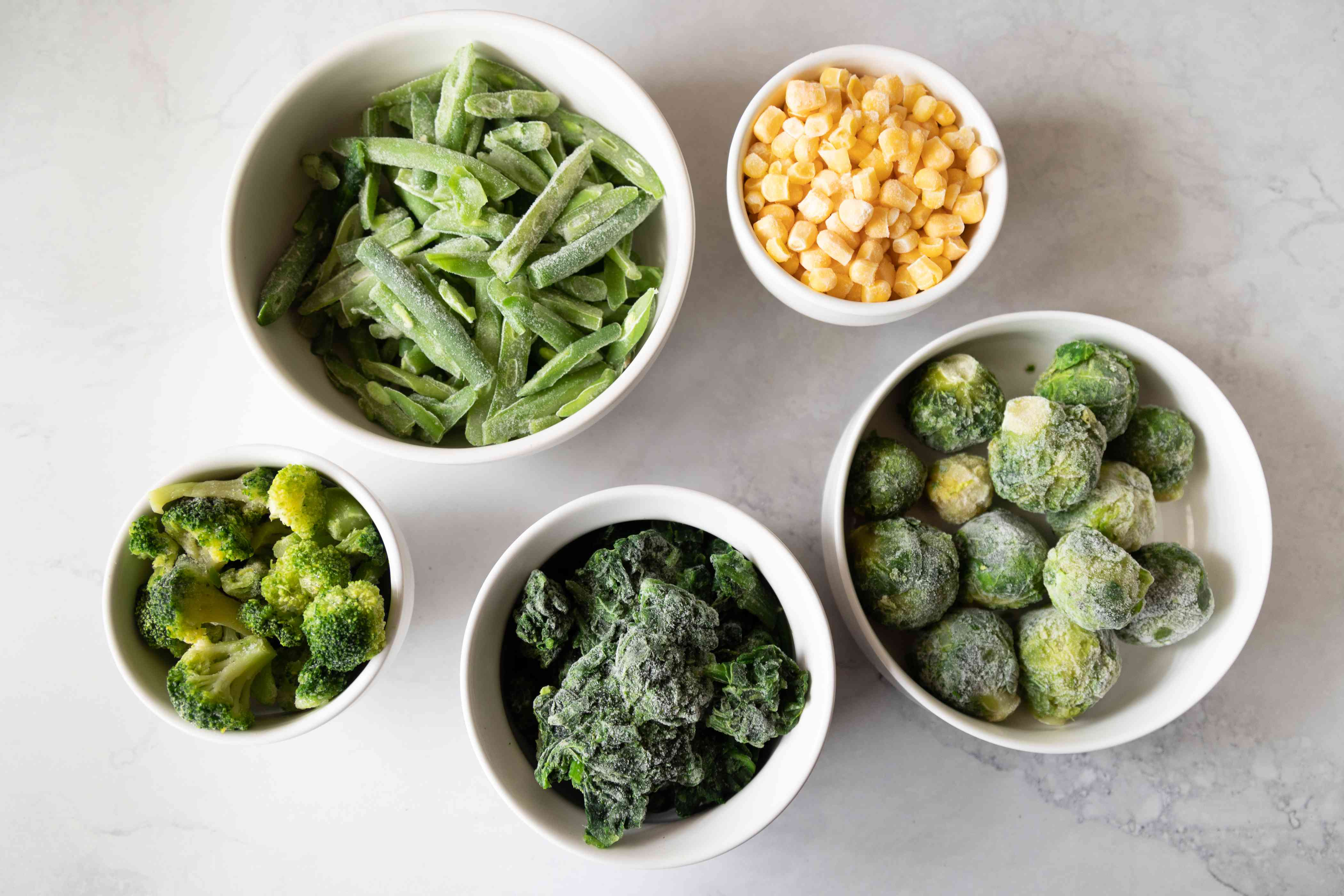 Frozen corn green beans broccoli brussels sprouts in white bowls