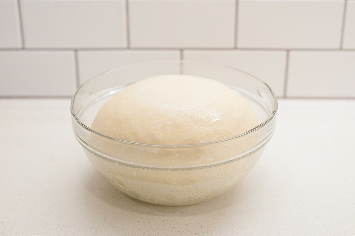 A glass bowl with lion house dinner roll dough rising inside.