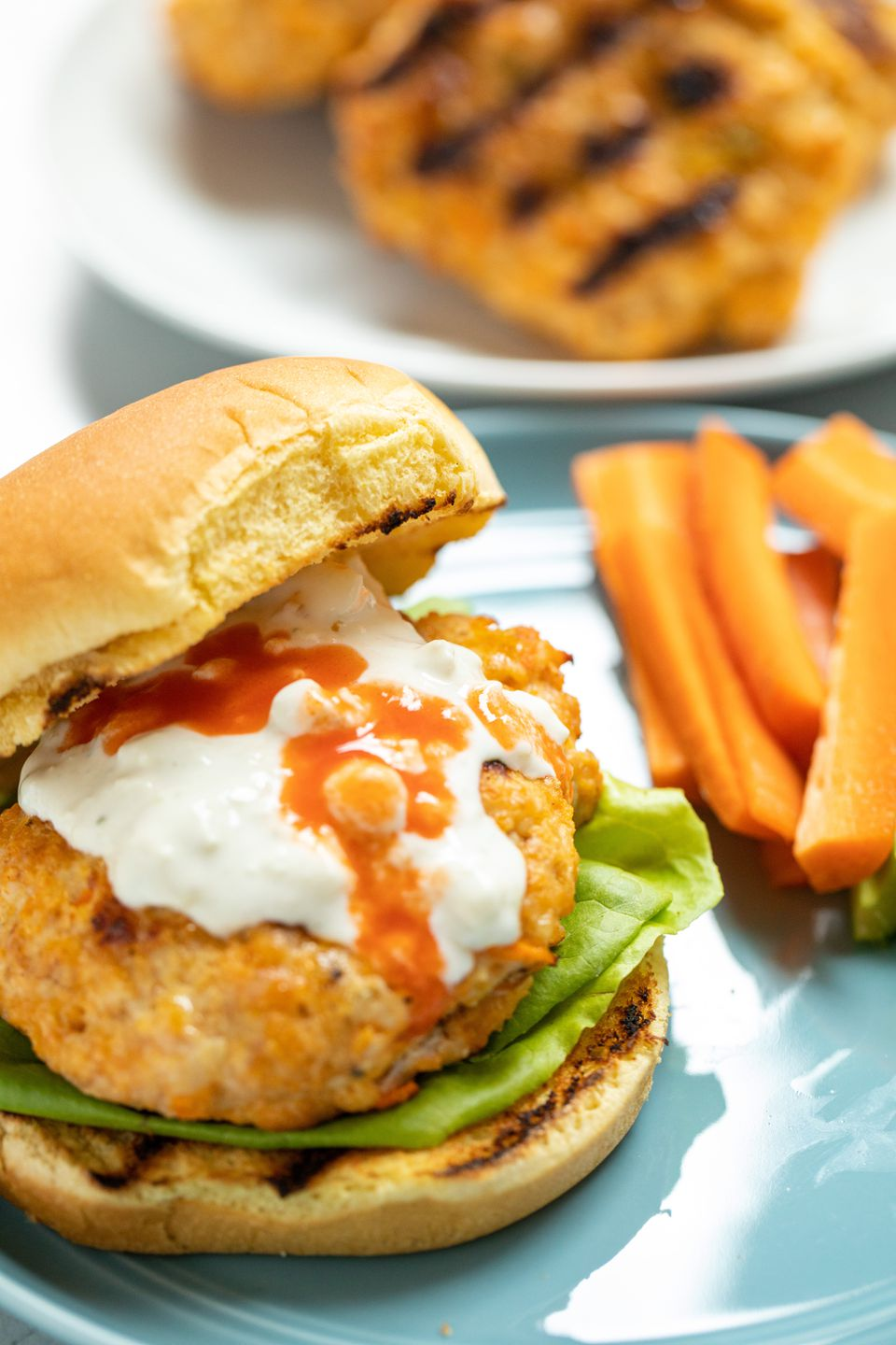The top bun set to the side of the BEST spicy buffalo chicken burger.