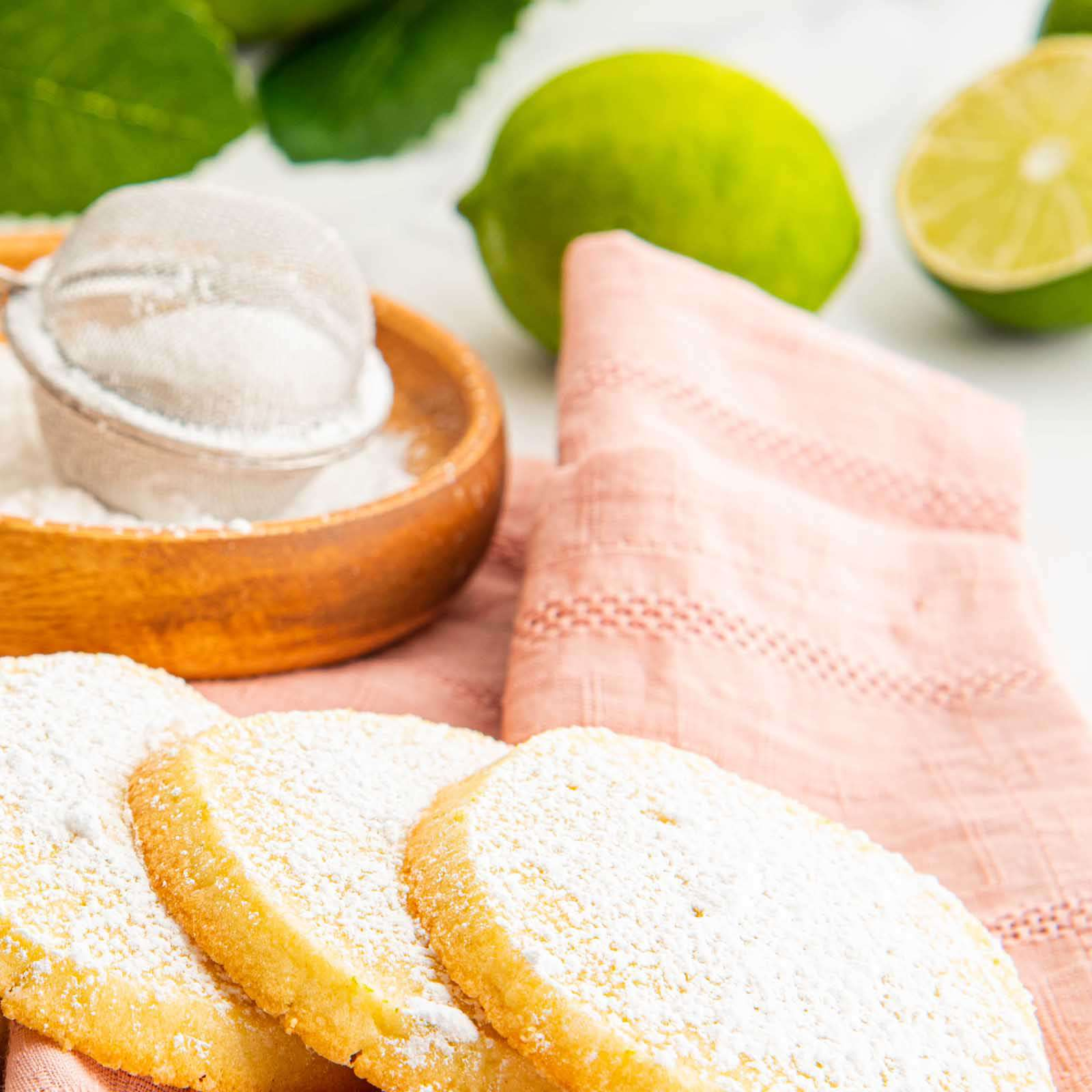 Close up vertical view of lime refrigerator cookies shingled on a pink linen with a wooden bowl of powdered sugar and a sifter behind it. A sliced lime and a lime branch are in the background.