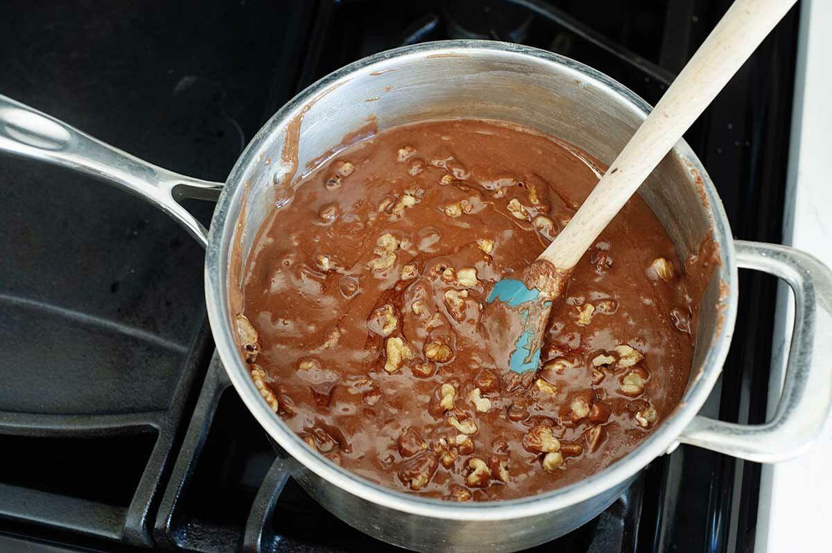 Homemade fudge in a saucepan with a spatula.