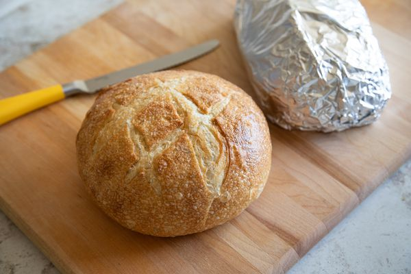 Bread loaf next to aluminum foil wrapped loaf
