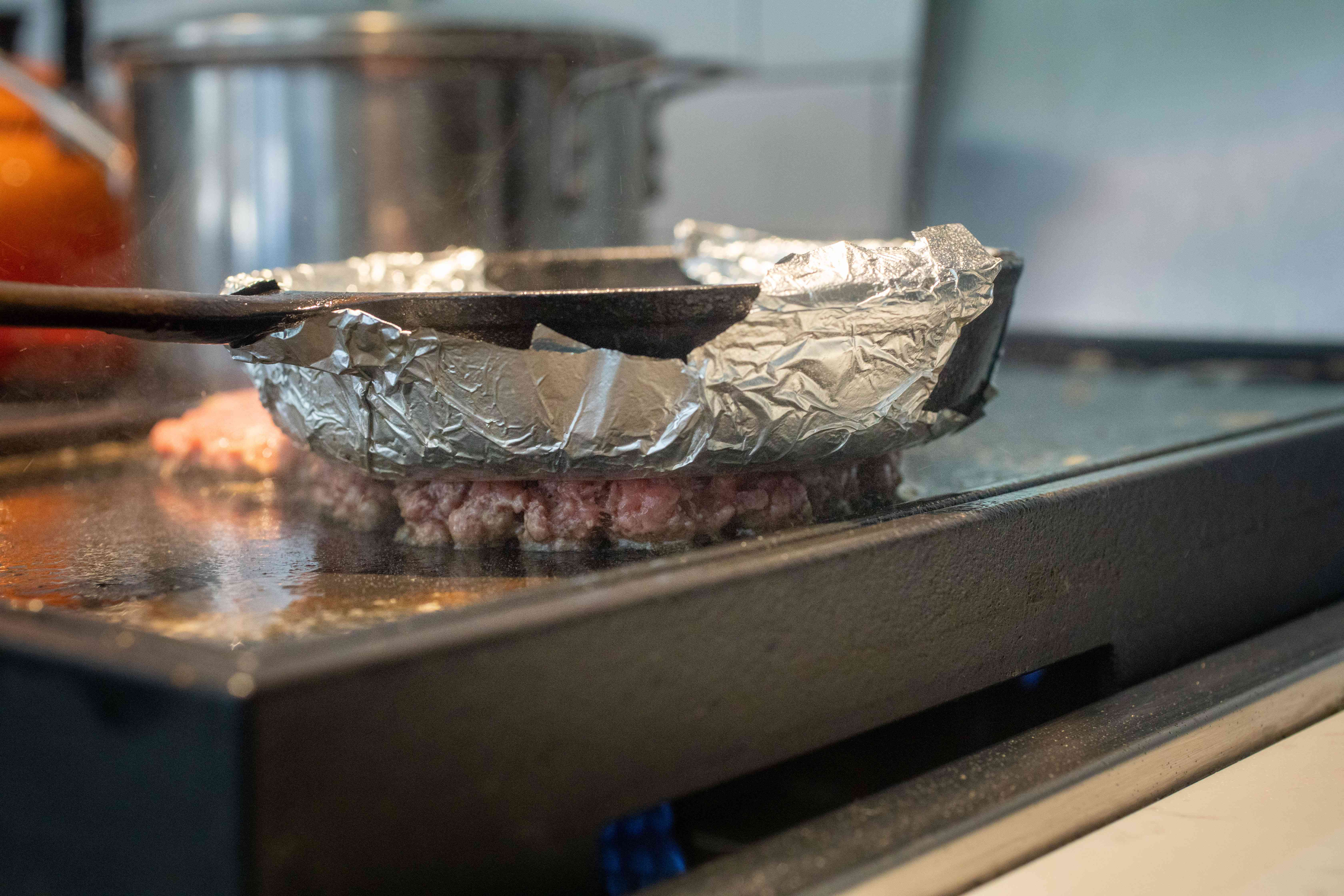 Skillet with foil wrapped around the bottom of it to make a Smashburger-style burger recipe.