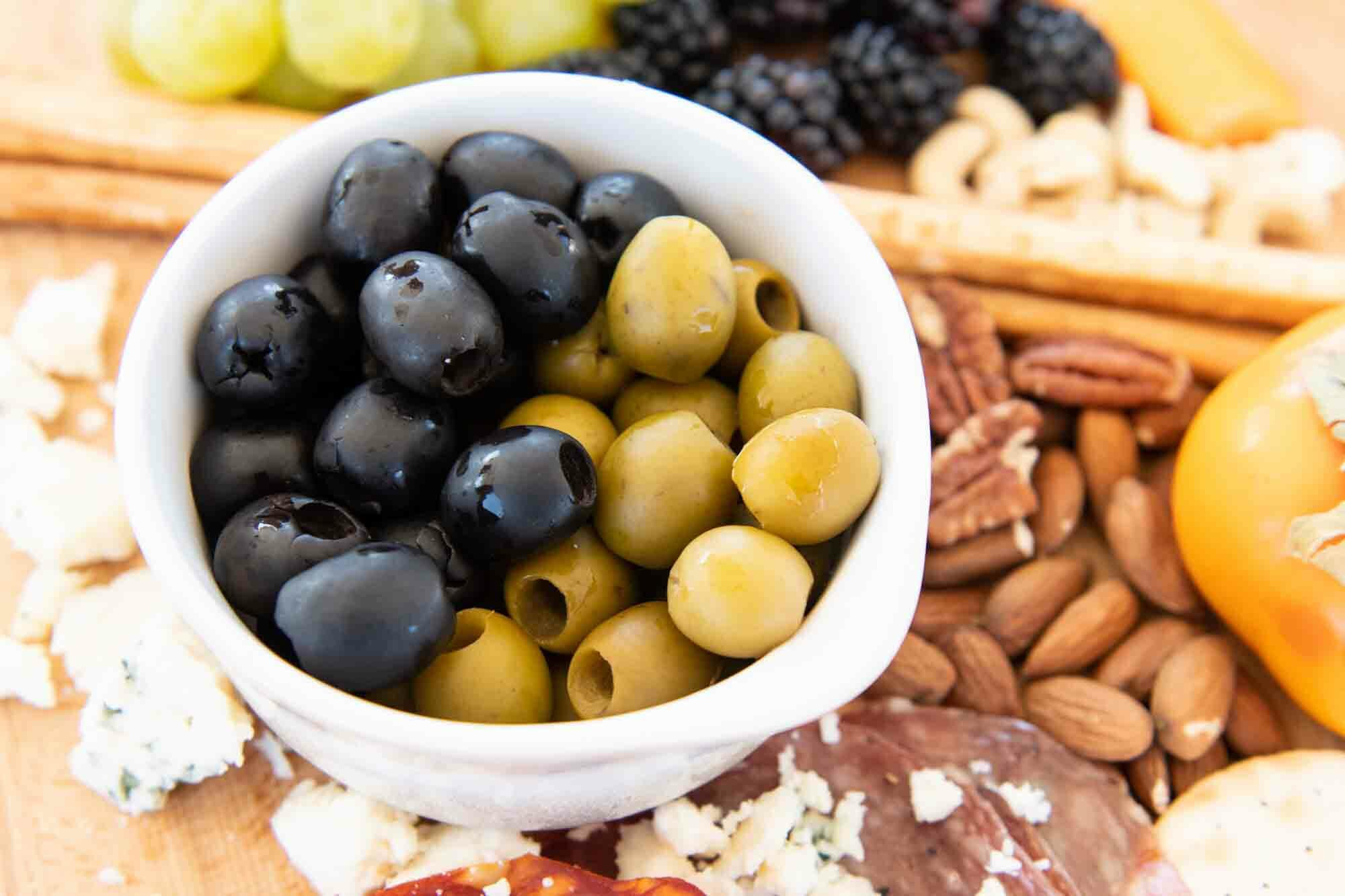 Green and black olives in a bowl on a cheese board