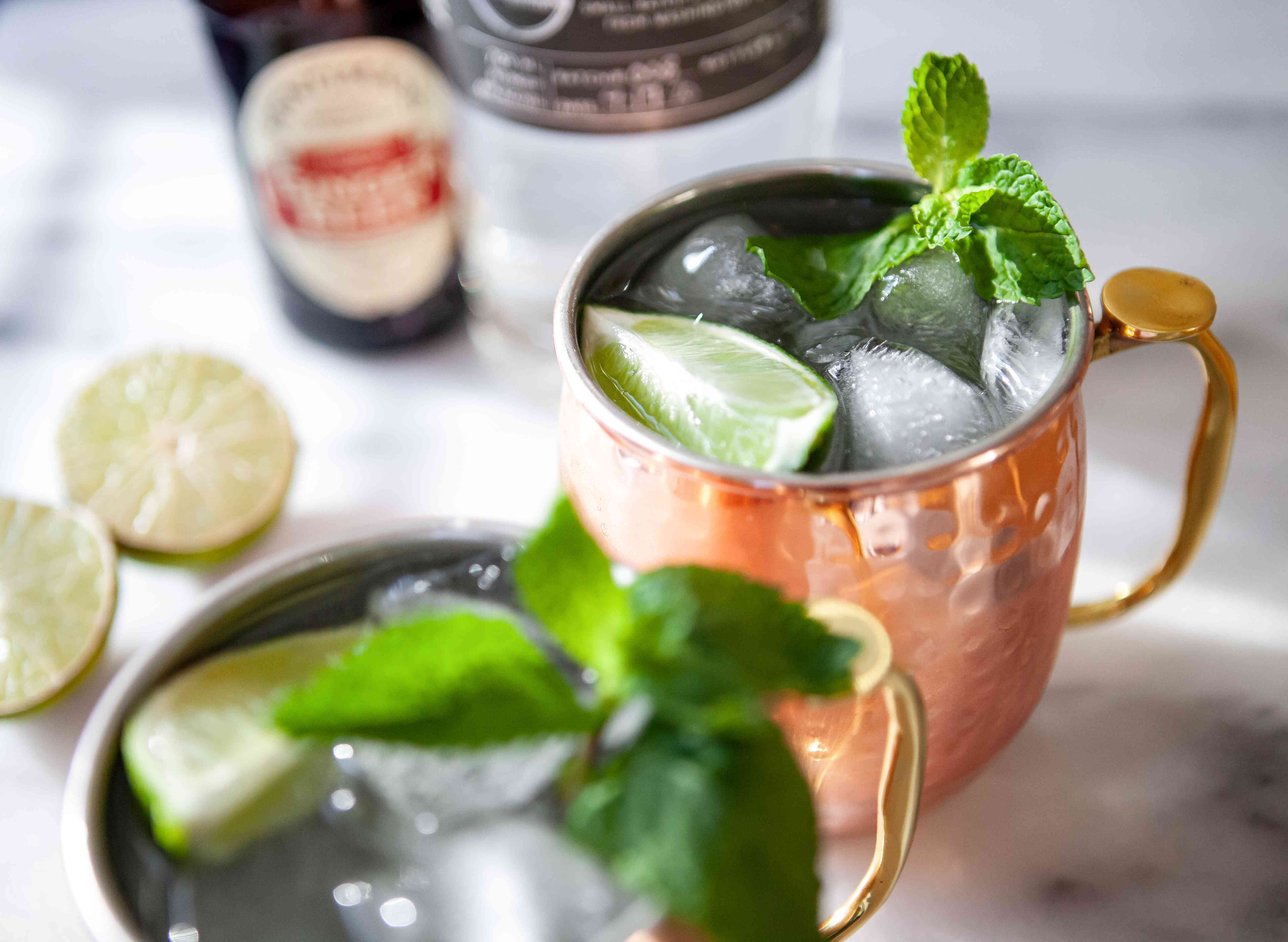 Copper cups with Moscow Mule Cocktails garnished with mint springs and lime wedges.