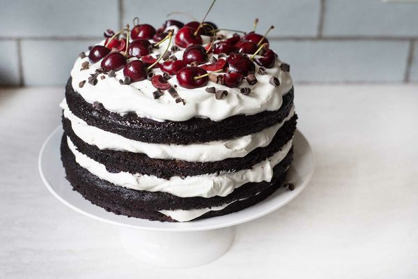 Side view of a Cherry Chocolate Cake with Whipped Cream on a white cake stand.