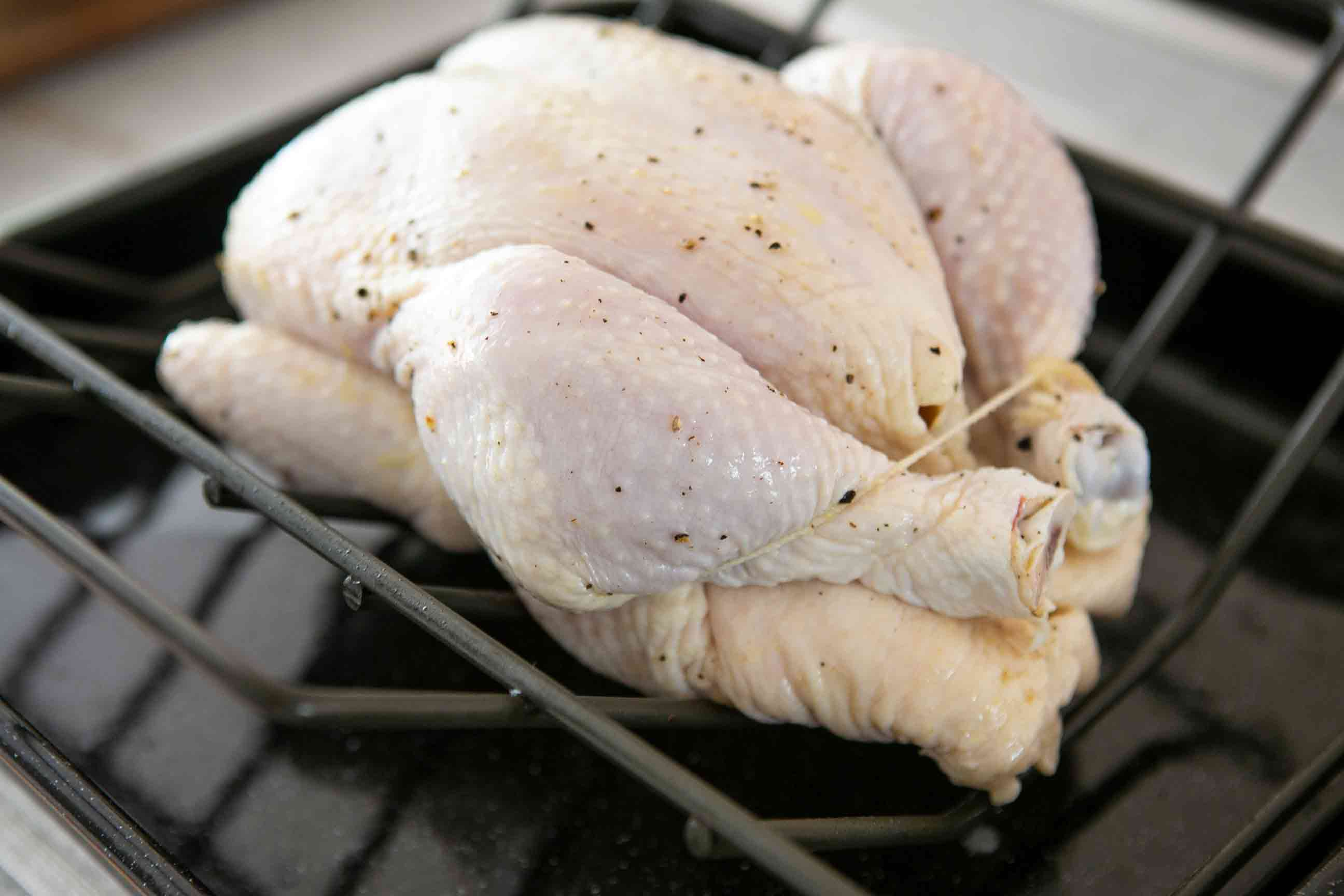 whole chicken trussed in roasting pan