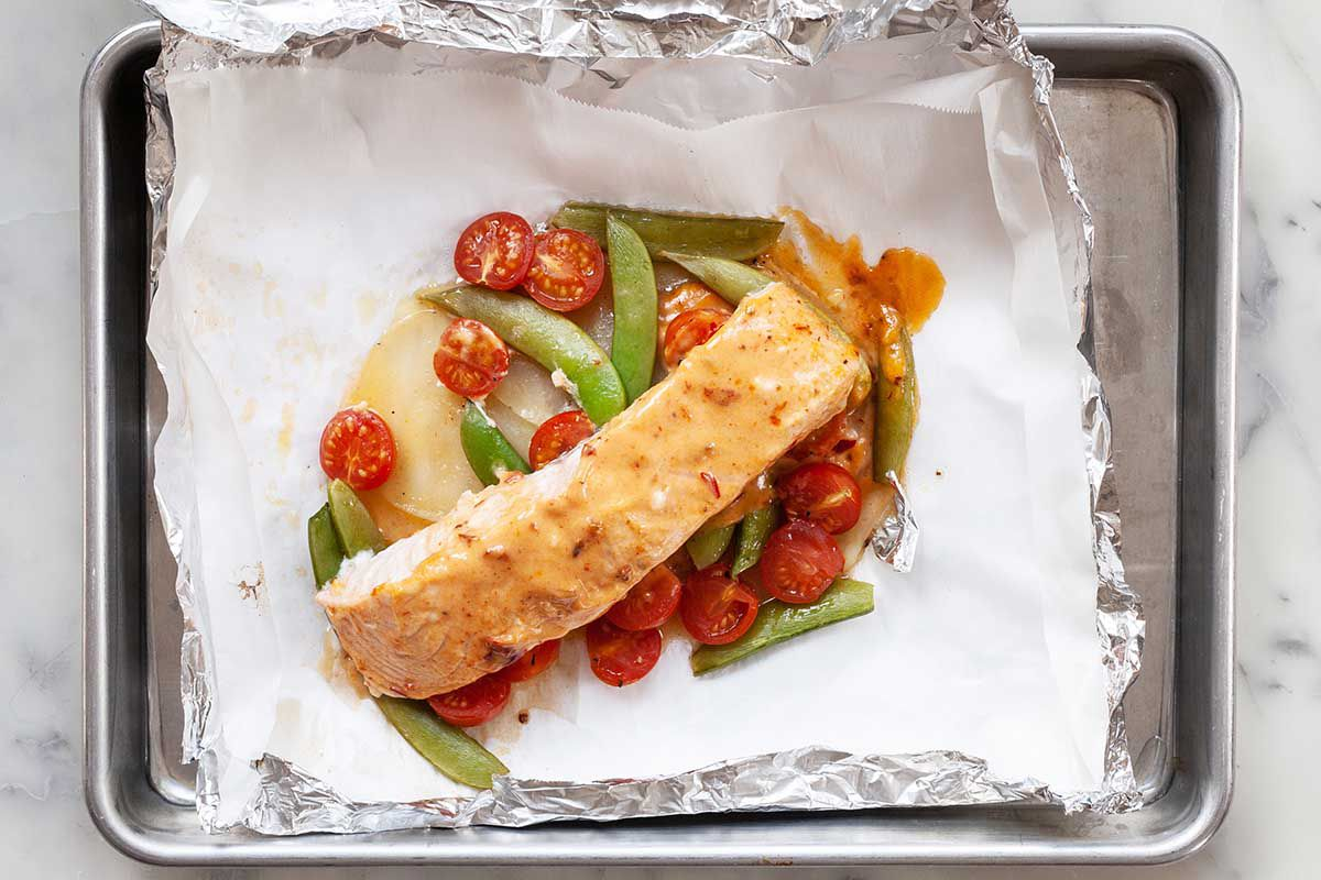 A baking sheet sits on a marble background, with a sheet of foil on it. Salmon filet rests on top of sliced grape tomatoes and sugar snap peas.