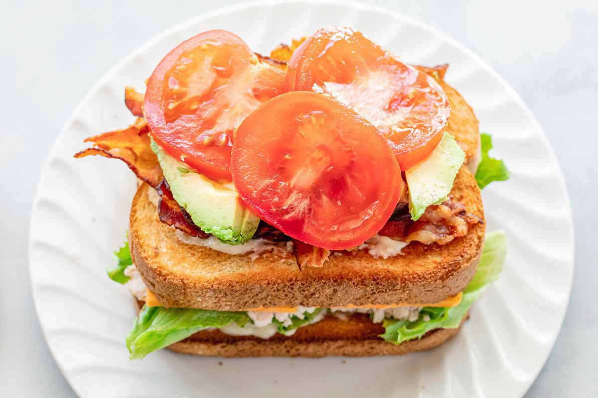 Homemade turkey club with two pieced of bread and tomato, bacon and avocado stacked on top of the toasted bread.
