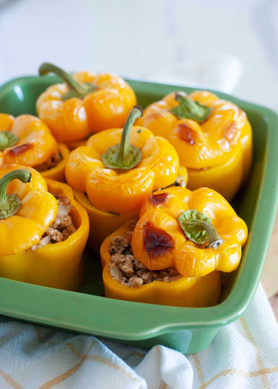 Close up of the casserole dish with the easy stuffed peppers inside. The tops of the peppers are slightly browned from the oven.