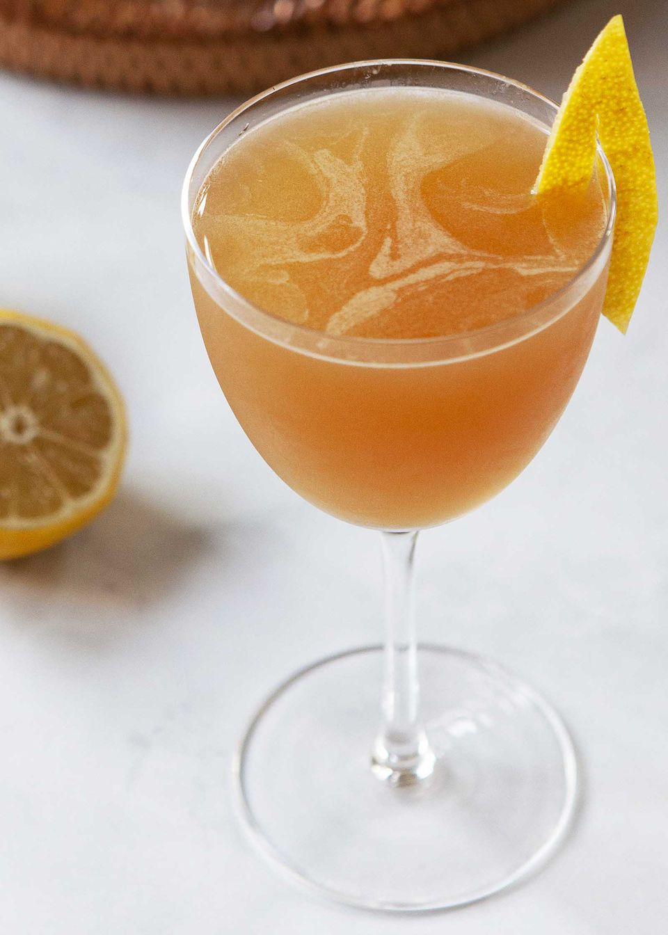 The best Sidecar cocktail with a lemon peel on the edge of the glass.
