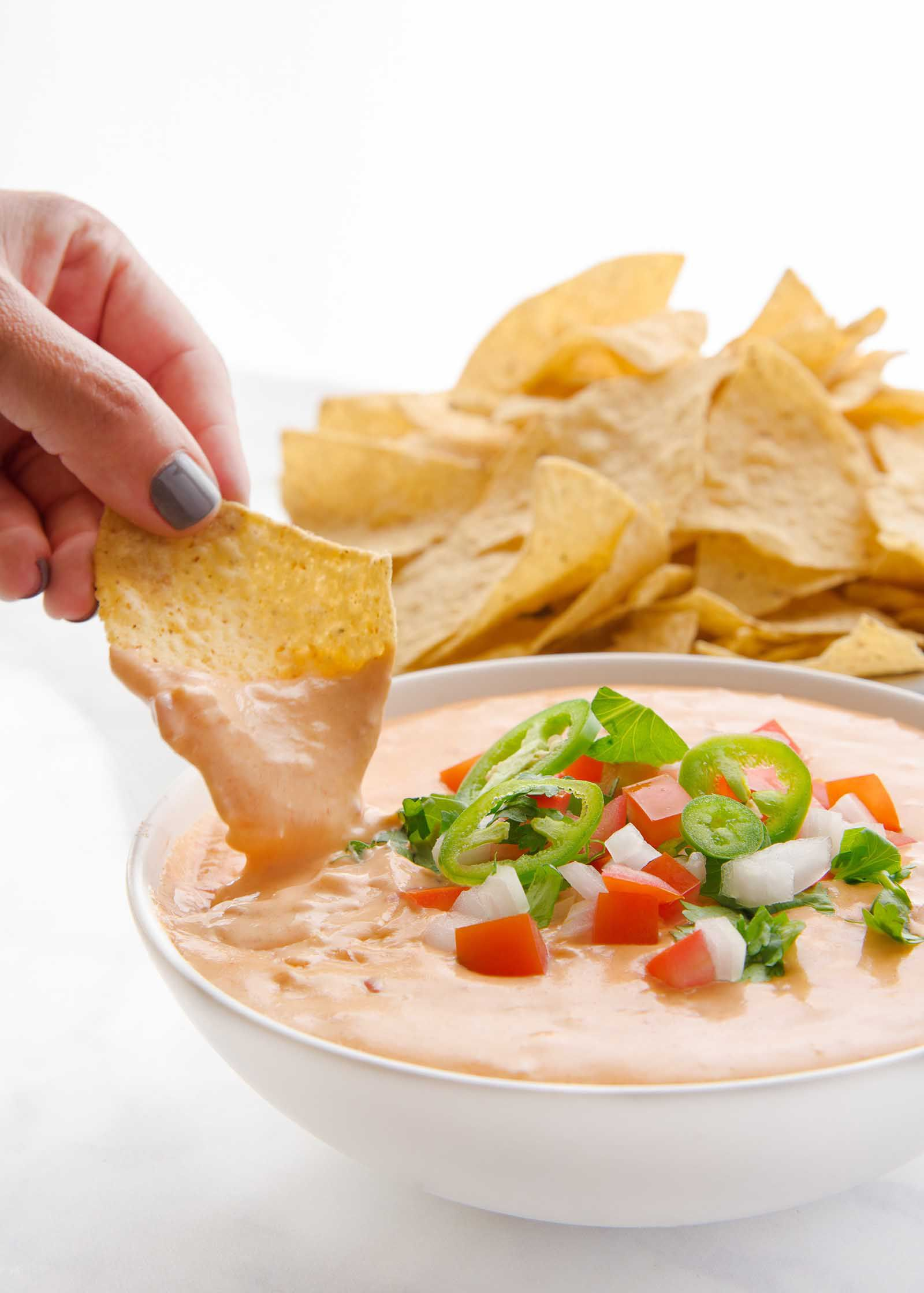 Hand scooping queso dip with pico de gallo and a bowl of tortilla chips nearby.