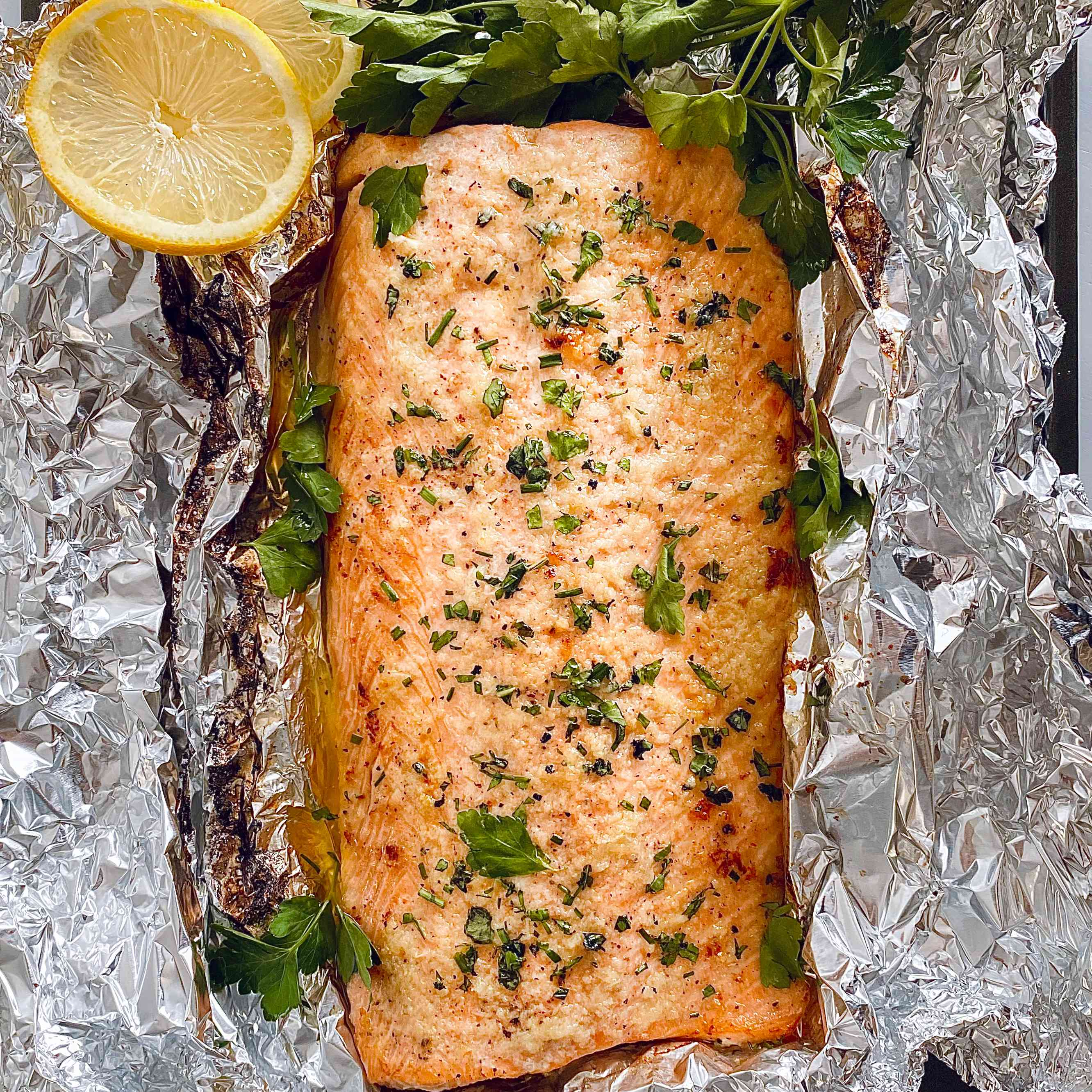 Garlic Butter Roasted Salmon on foil with herbs and lemon.