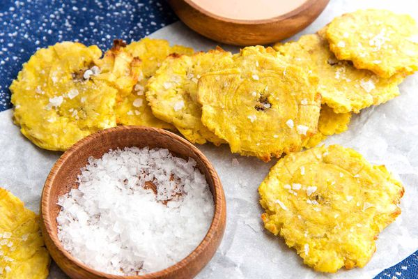 Air Fryer Tostones on parchment paper with a bowl of salt nearby.