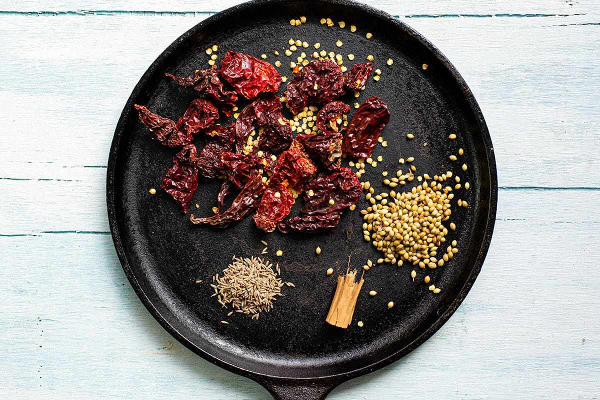 A black plate with dried peppers and spices scattered about.