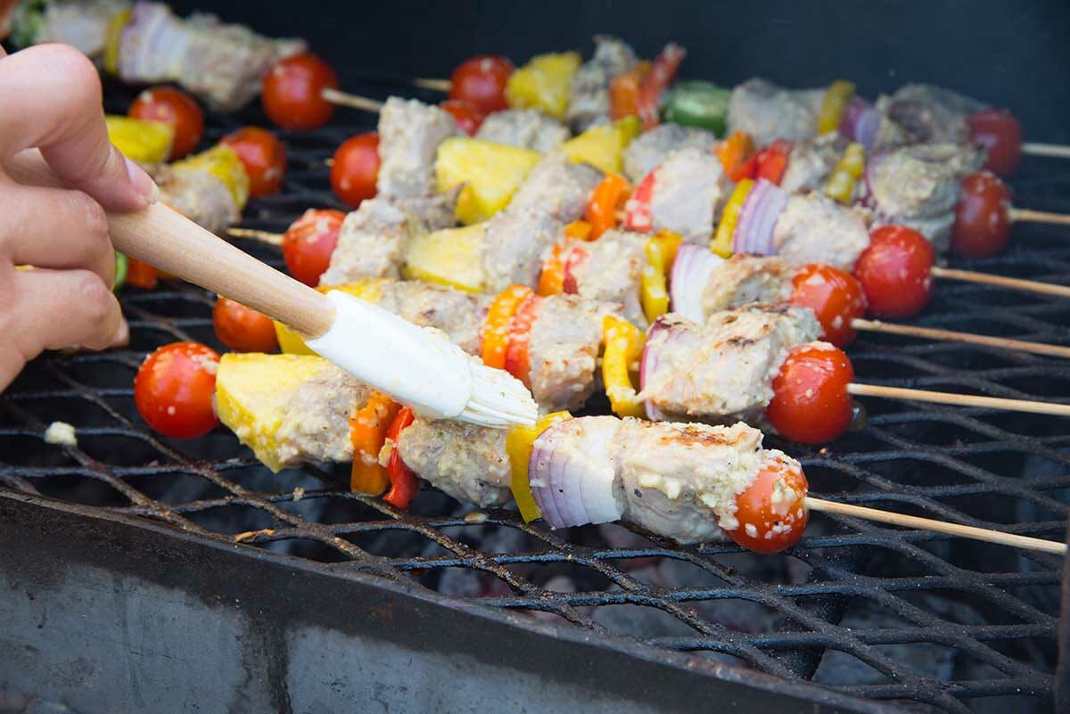 Pork kebabs with mojo marinade on the grill and being brushed with mojo marinade.