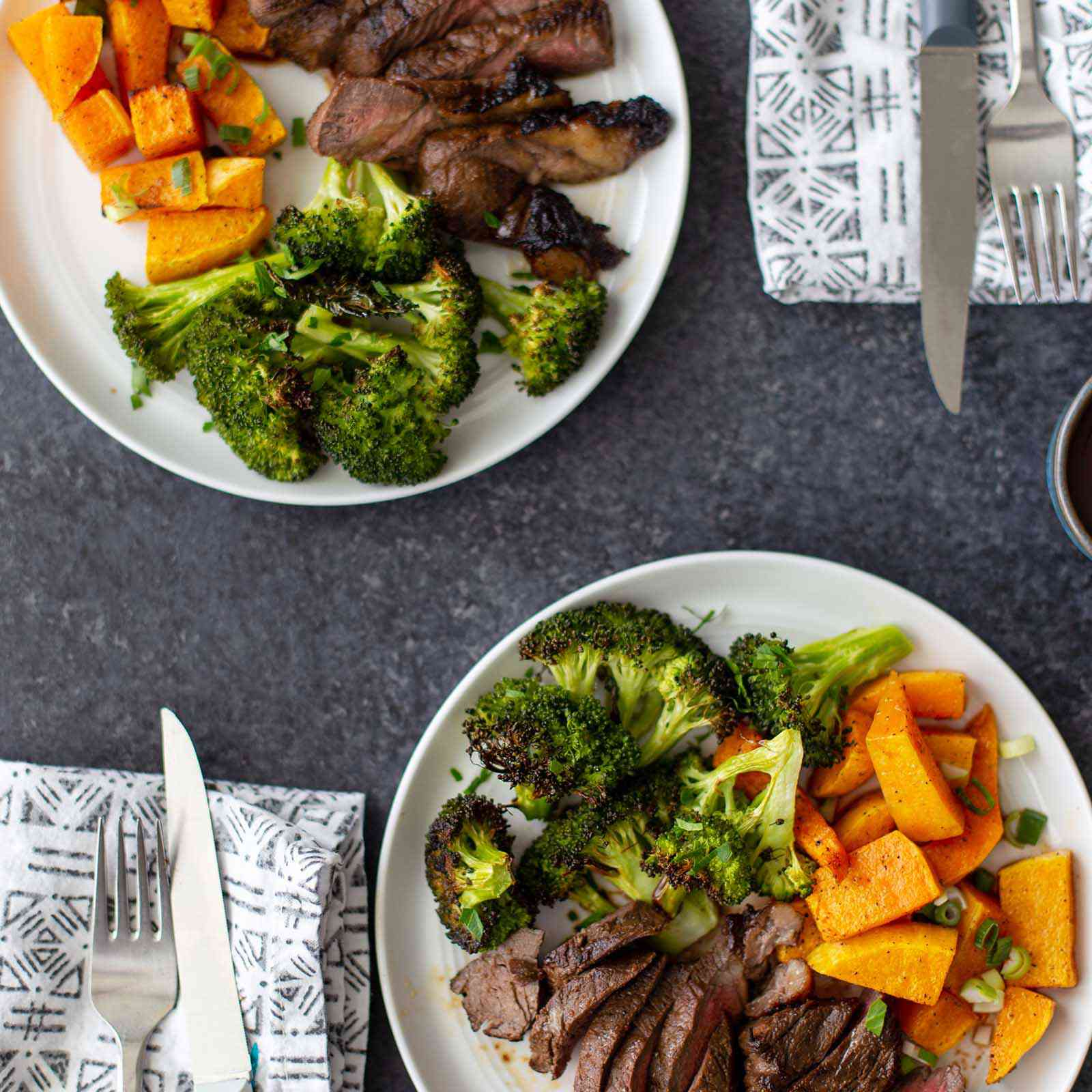 Two plates with sliced easy broiled steak, chopped broccoli and squash. Silverware and a linen are next to each plate.