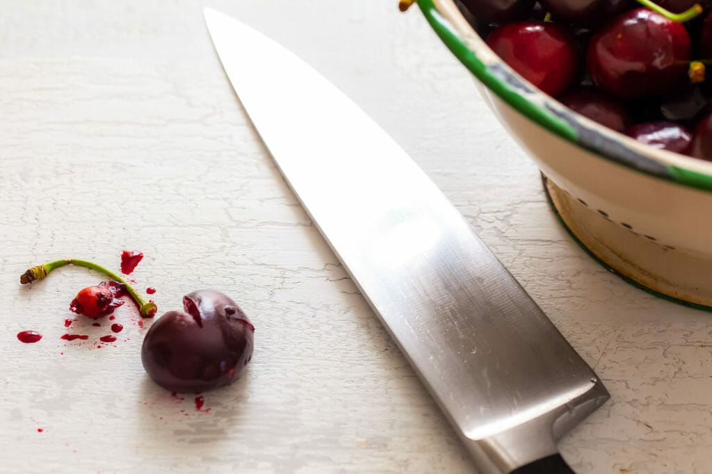 A chef's knife with a partially split cherry with the stem and pit romoved is to the left. A large bowl of cherries is to the right showing the best way to pit cherries.