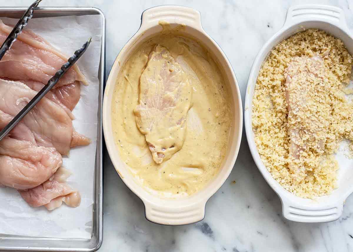 preparing raw chicken breasts for baked chicken parmesan dish