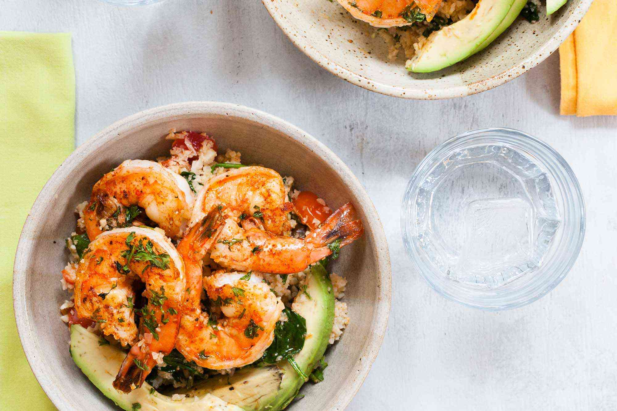 A horizontal poto of cauliflower rice and shrimp. A green napkin is to the left and a water glass to the right. Above the glass is a second bowl in partial view.