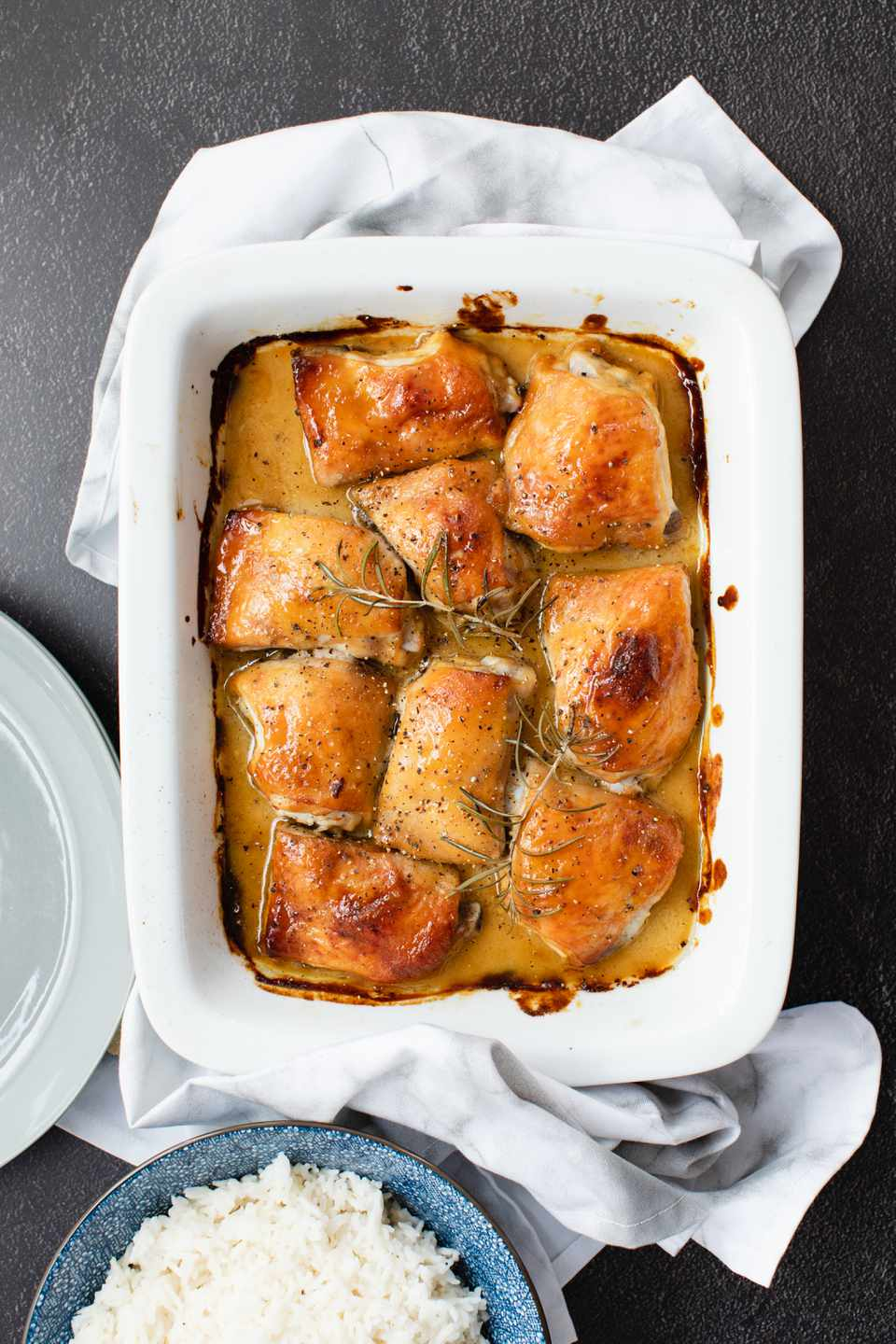 Overhead view of baked chicken in a casserole dish.