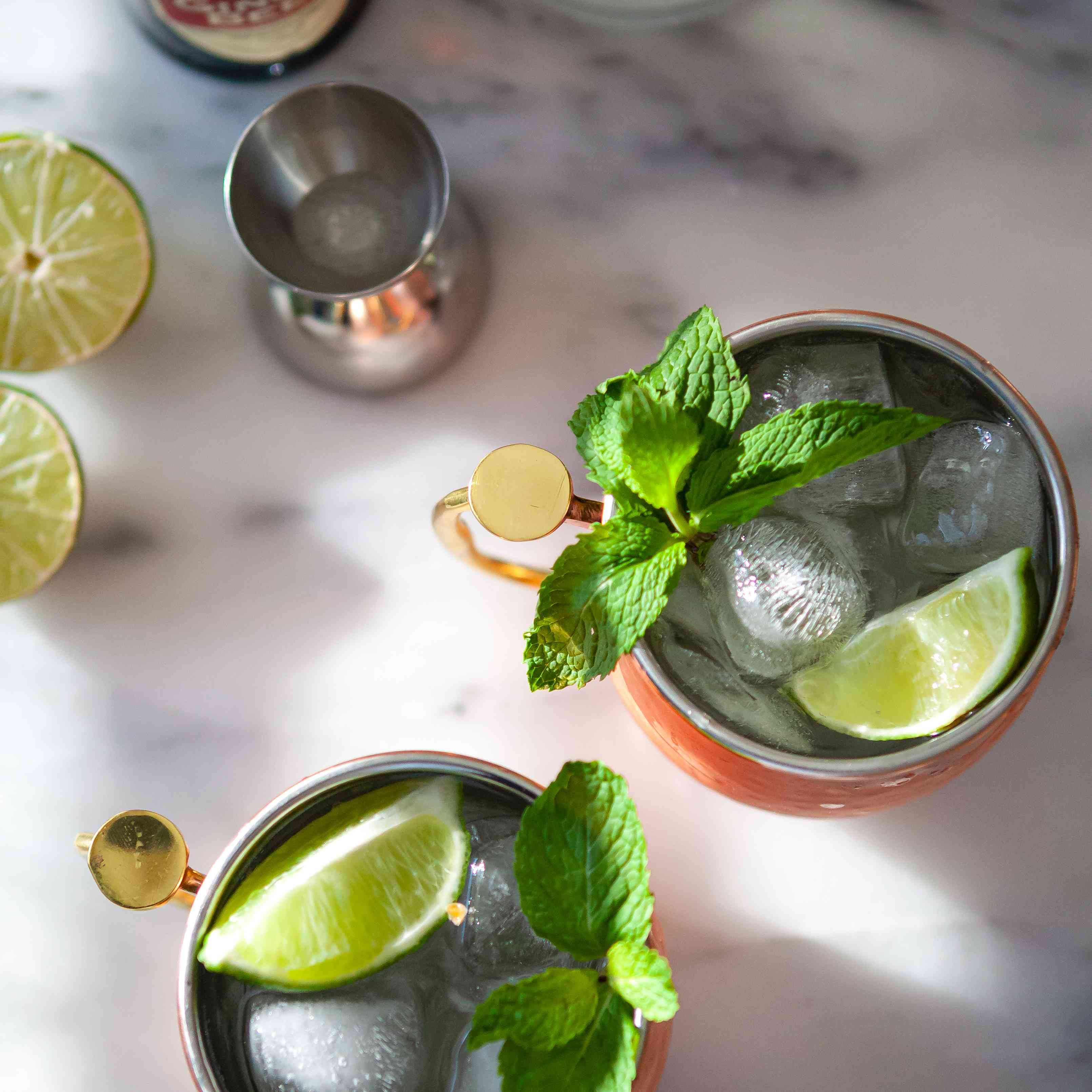Overhead view of two of the BEST Moscow Mule cocktails with bottles and sliced lime in the upper left.