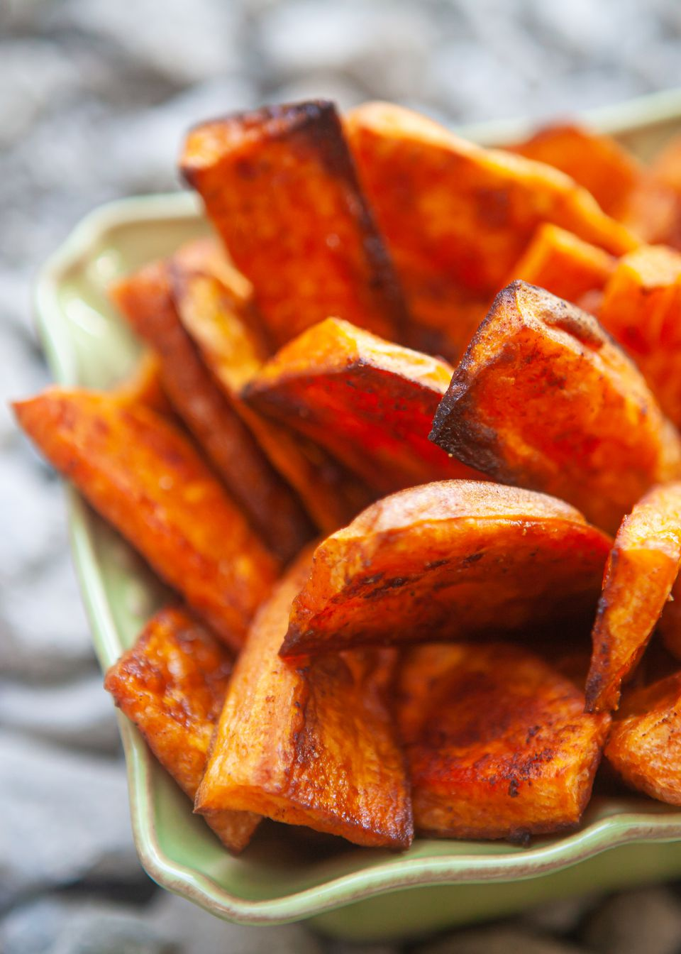 Baked sweet potato fries stacked in a container.