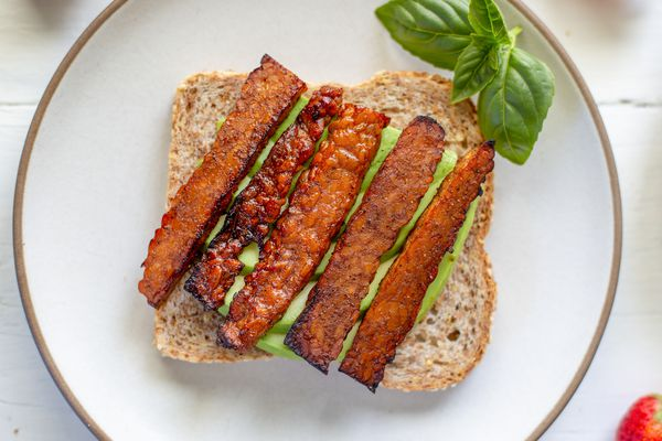 Overhead view of vegetarian bacon on a piece of bread with avocado underneath it.