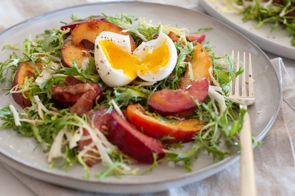 Side view of a summer-y salad with stone fruit and frisée.
