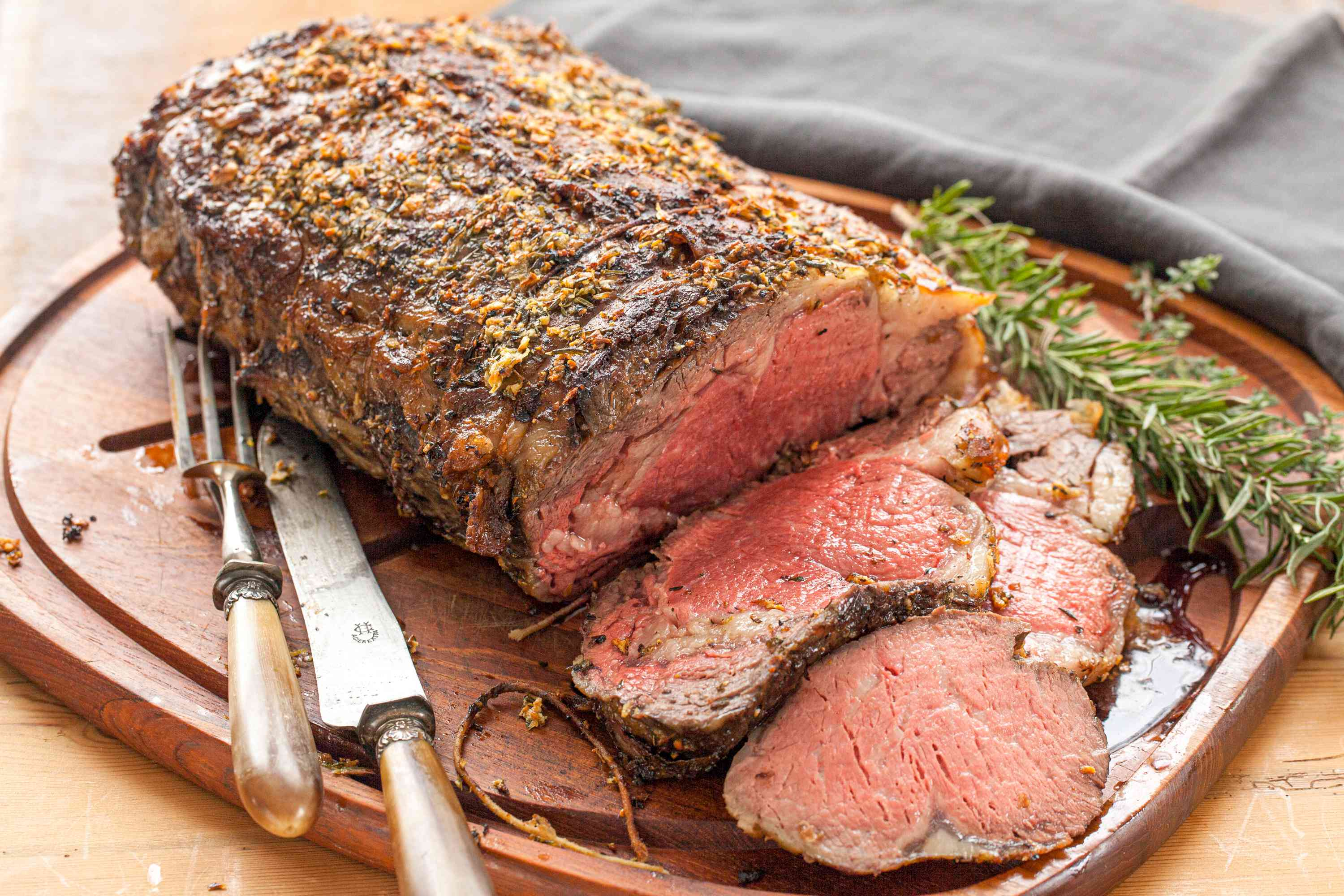 Herb butter prime rib with gravy being served on a cutting board.