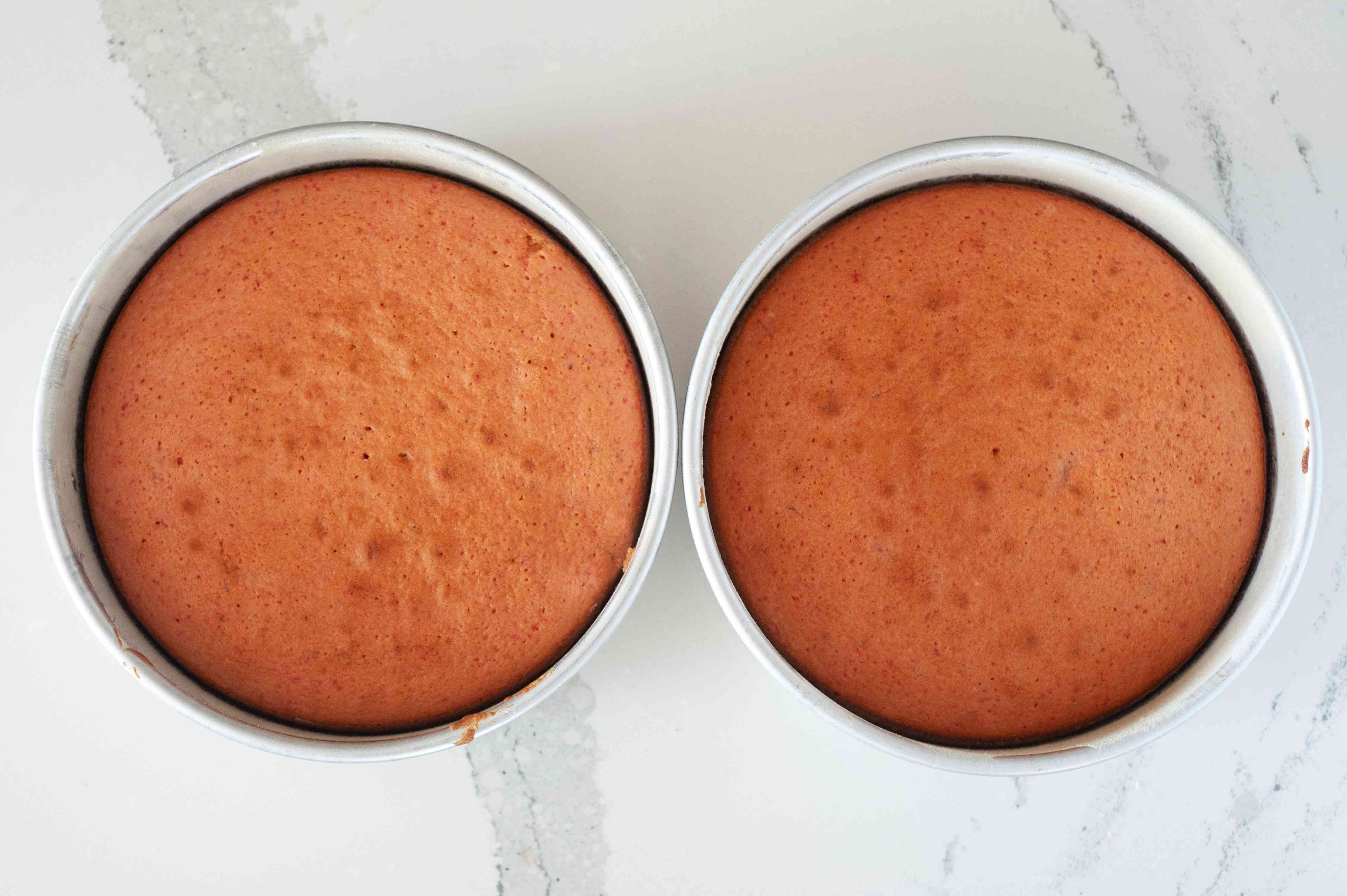 Two baked strawberry cake layers in cake pans.