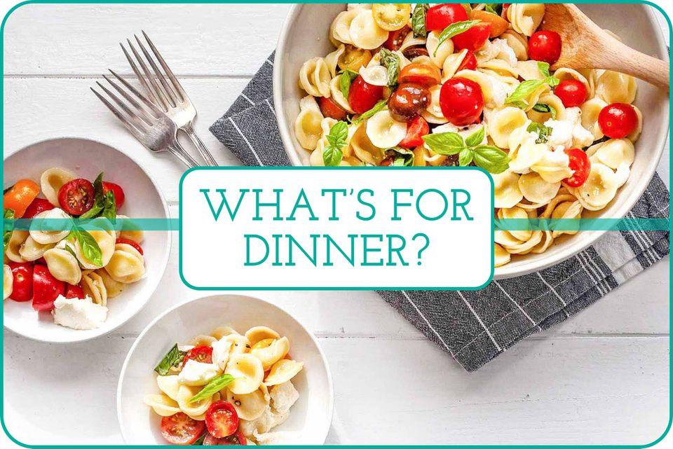 A large serving bowl with Caprese Pasta Salad and two smaller bowls, two forks and a linen.