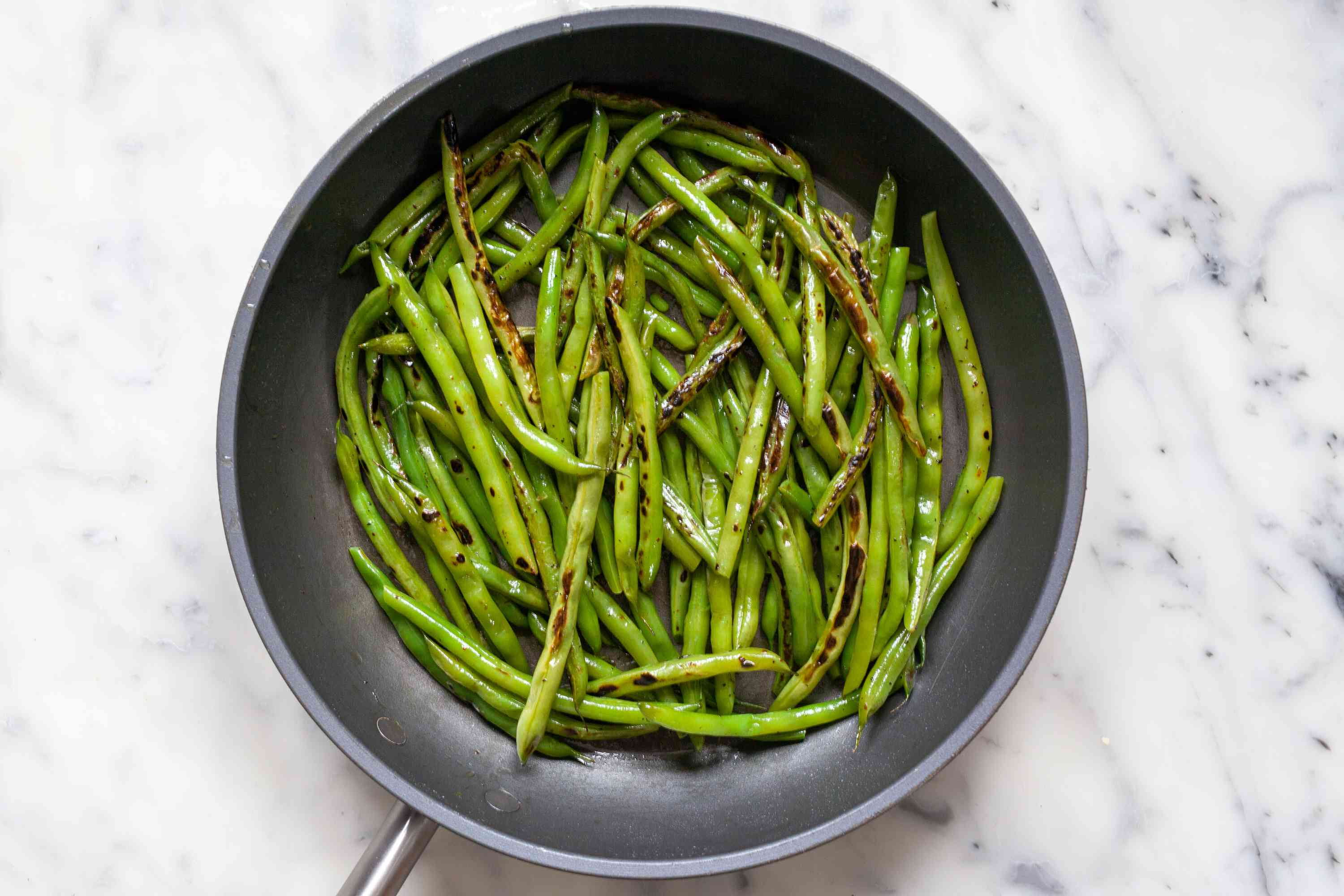 Spicy Korean Blistered Green Beans with Gochujang cooked in a skillet.