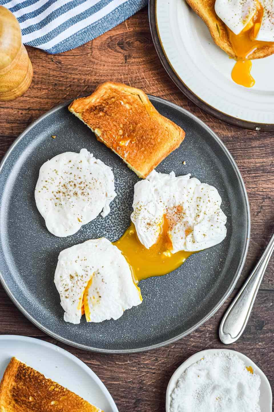 Three poached eggs and a piece of toast on a table with linens, plates, forks, and pepper grinder.