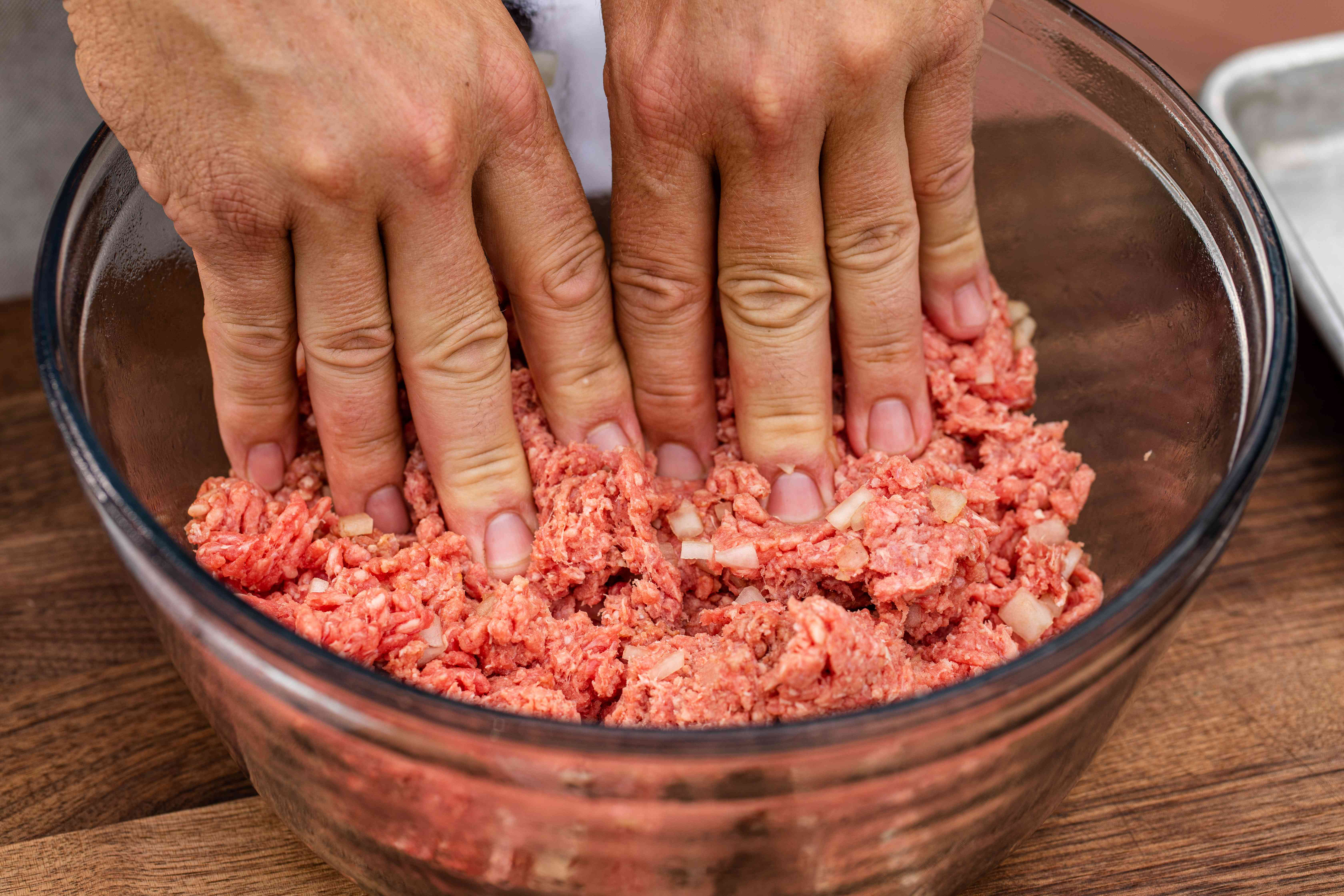 Using hands to mix in ingredients to make a classic bacon cheeseburger