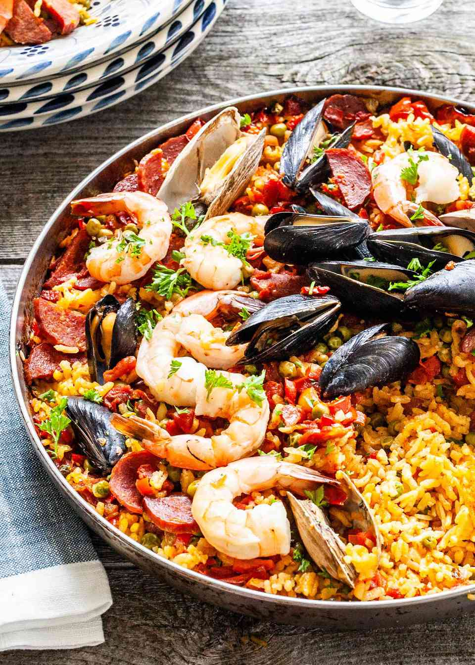 Paella recipe with seafood, cooked on the grill and served in a skillet