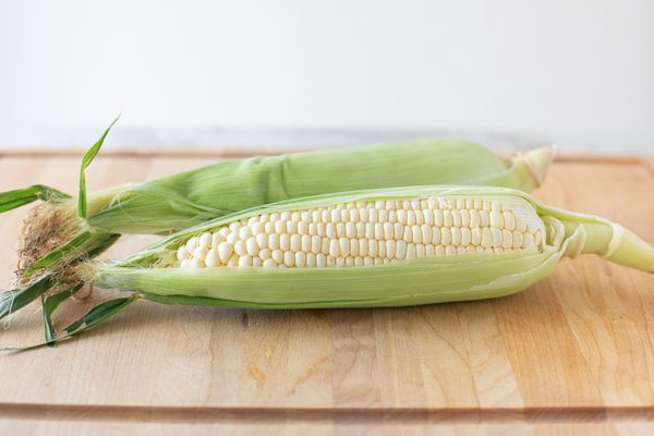 Two ears of corn with husk pulled back showing kernals on a wood cutting board