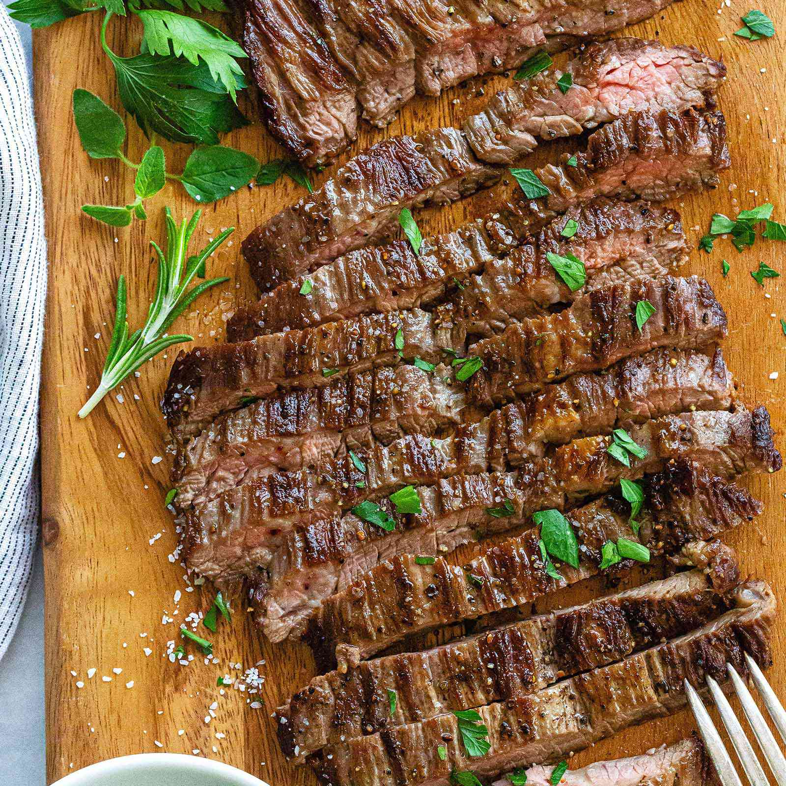 How to Cook Skirt Steak in a Pan - sliced steak with herbs on top